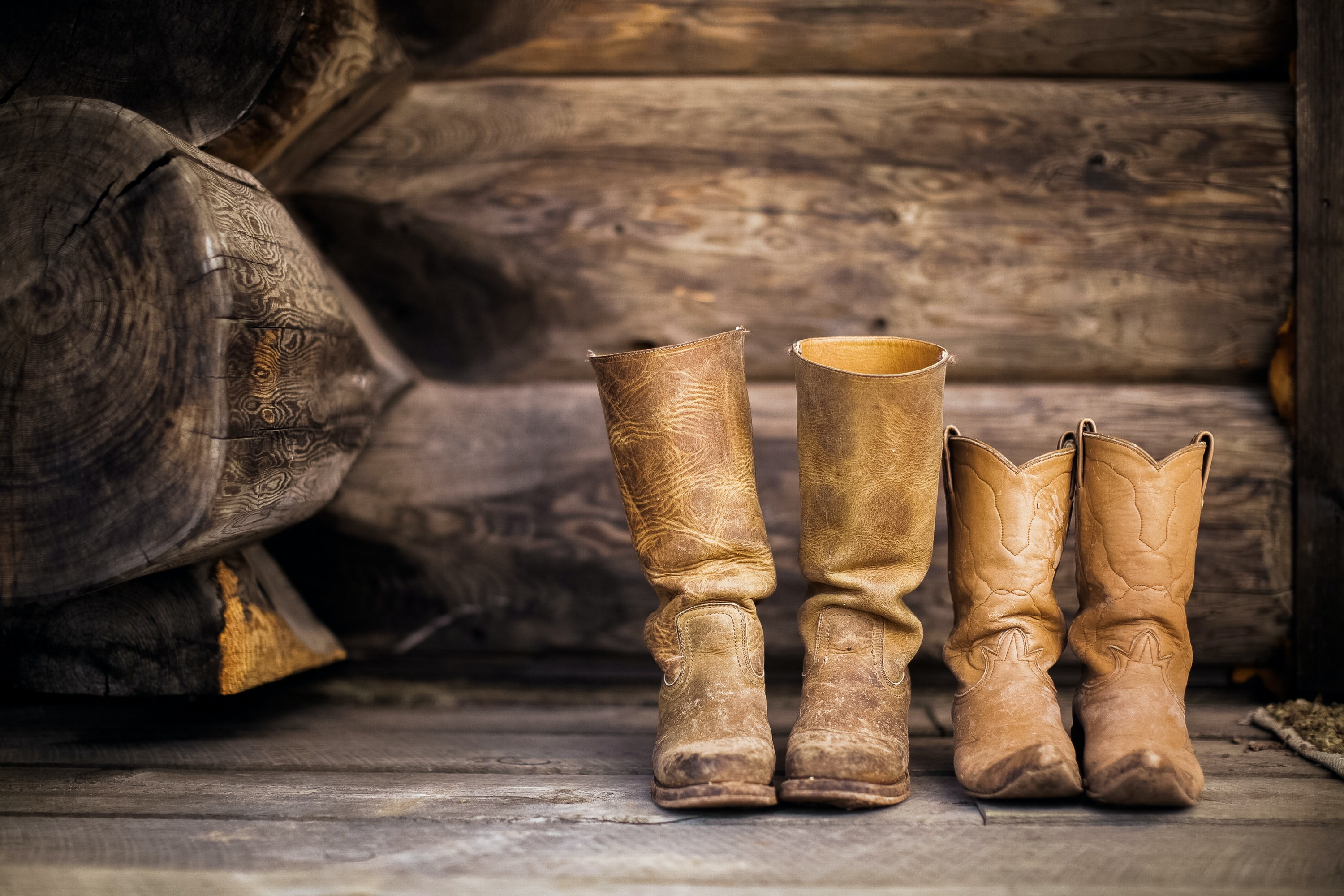 two pairs of worn in cowboy boots set in front of wooden logs