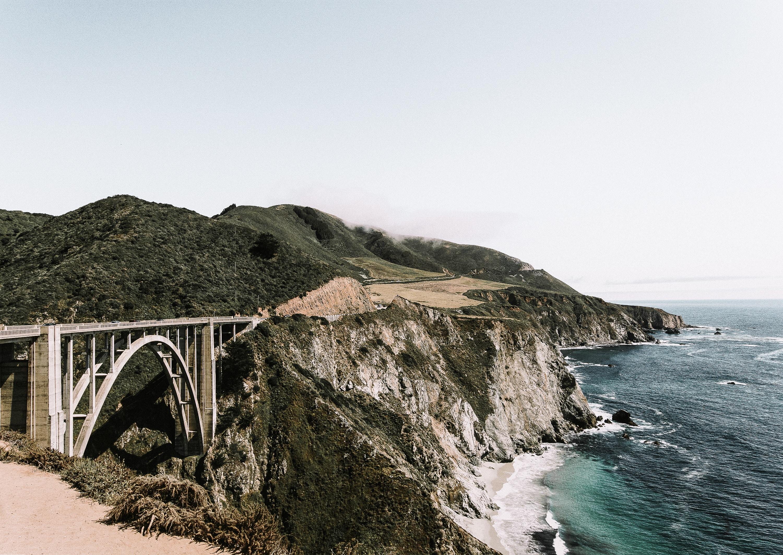 photo of white bridge on mountain