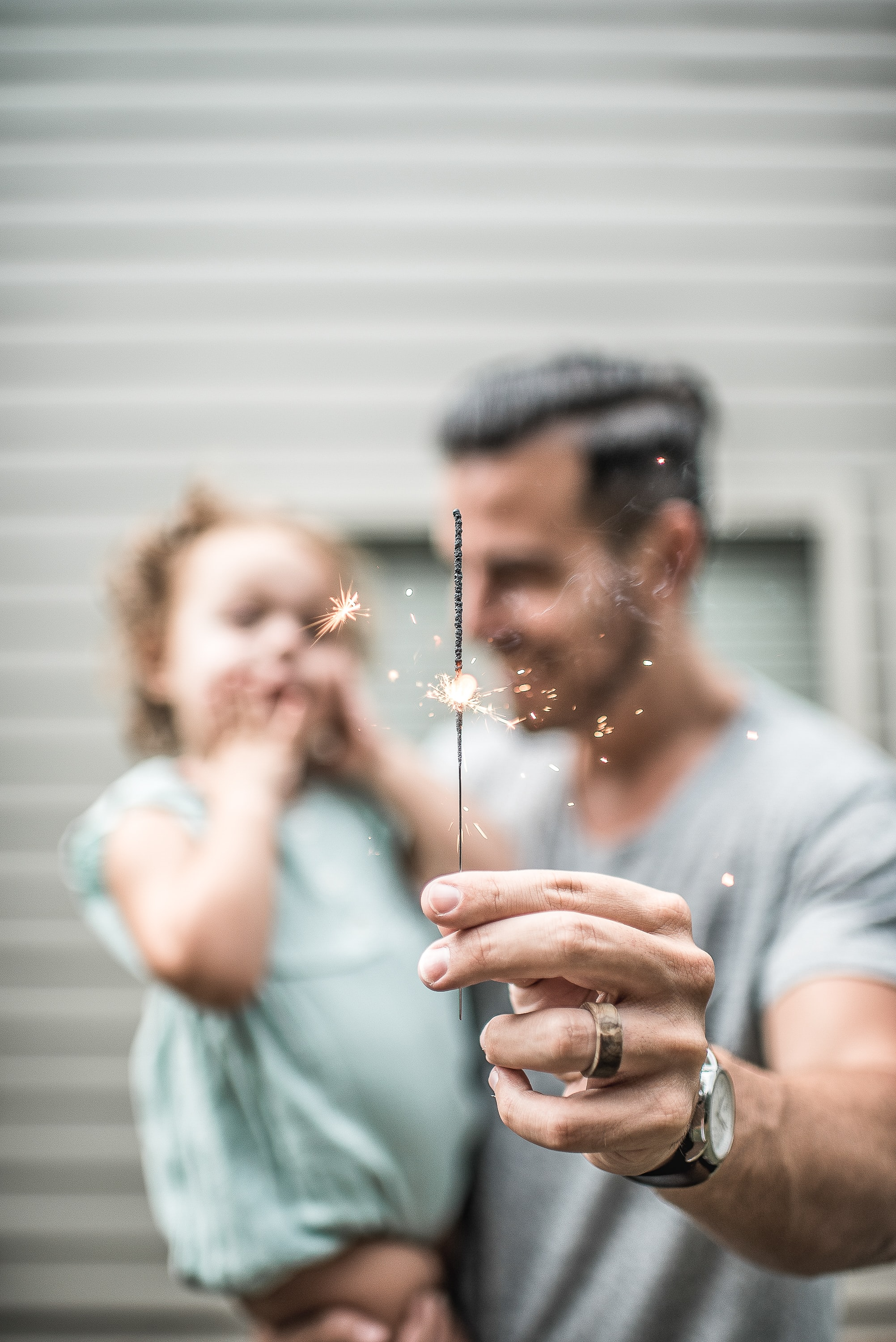 Sharply in foreground, a father's hand holds up a sparkler as he holds his delighted daughter in other