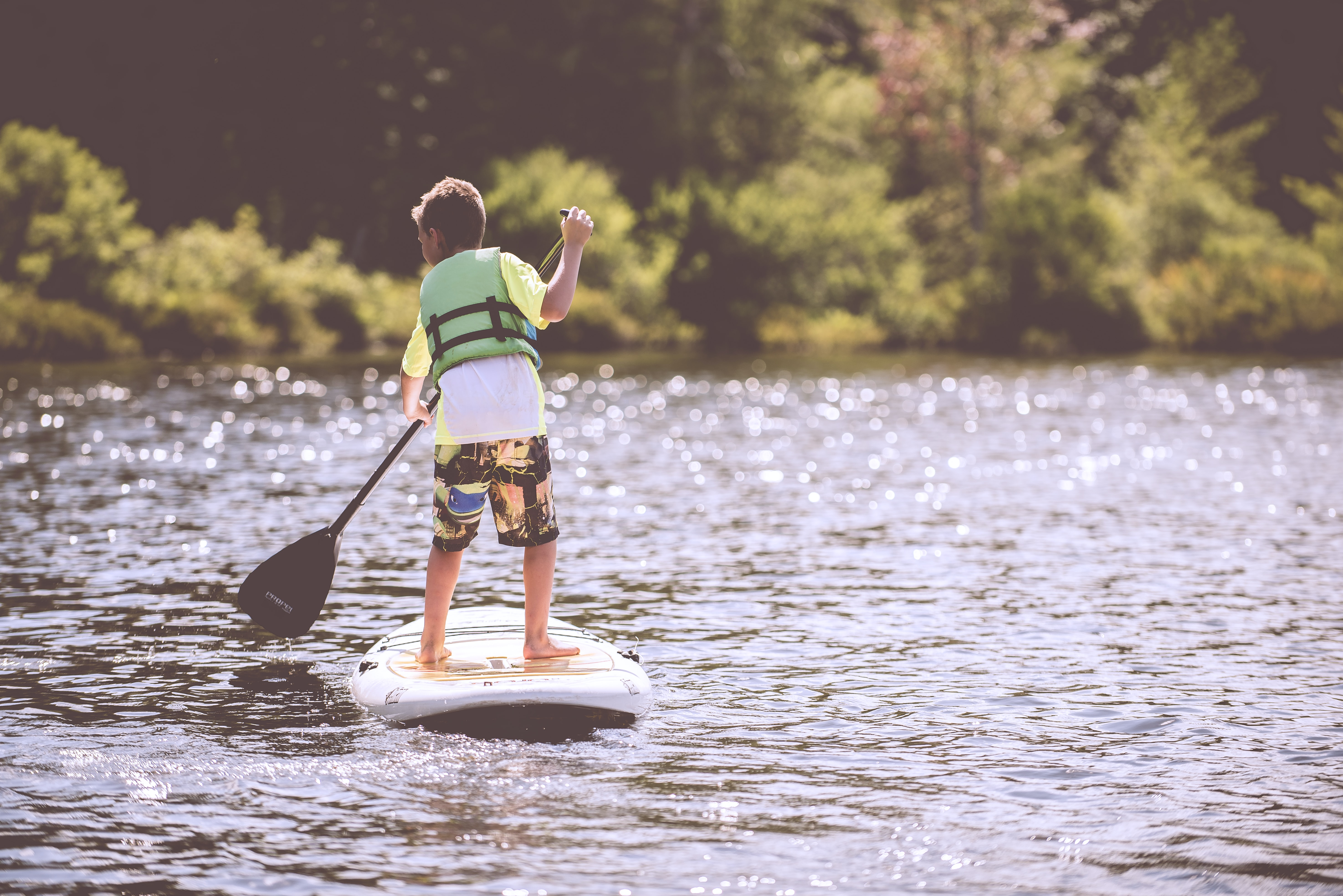 A boy wearing a bathing suit and a green life jacket paddleboarding