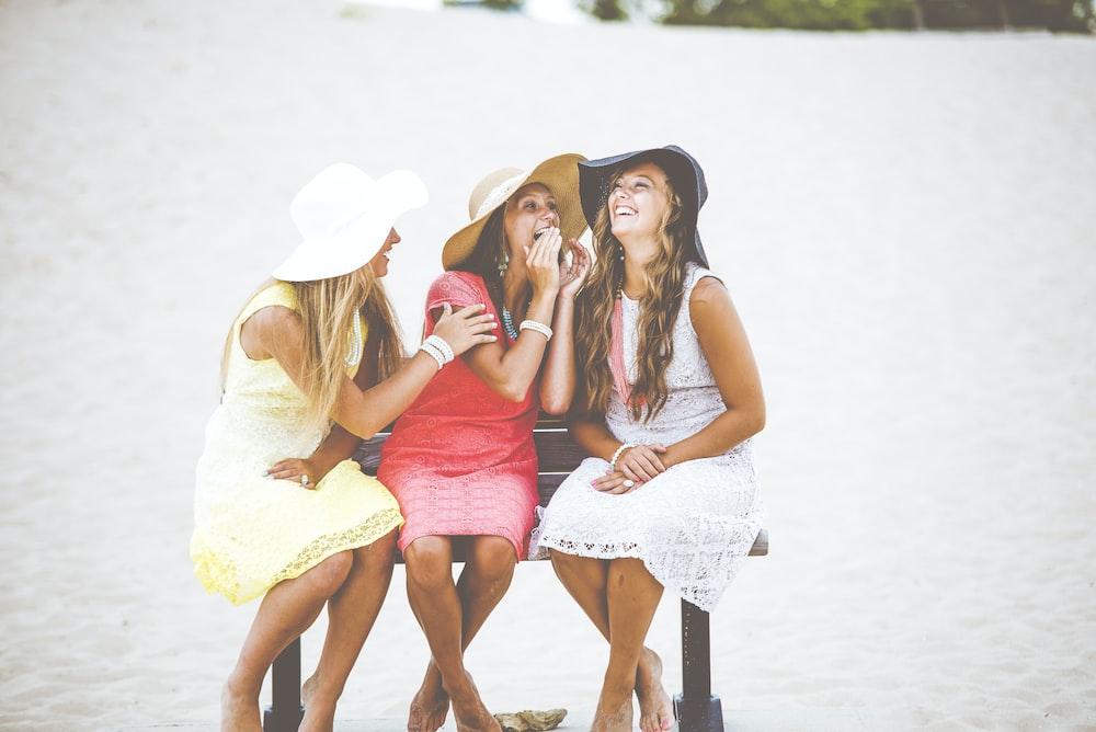 three women sitting on brown wooden bench