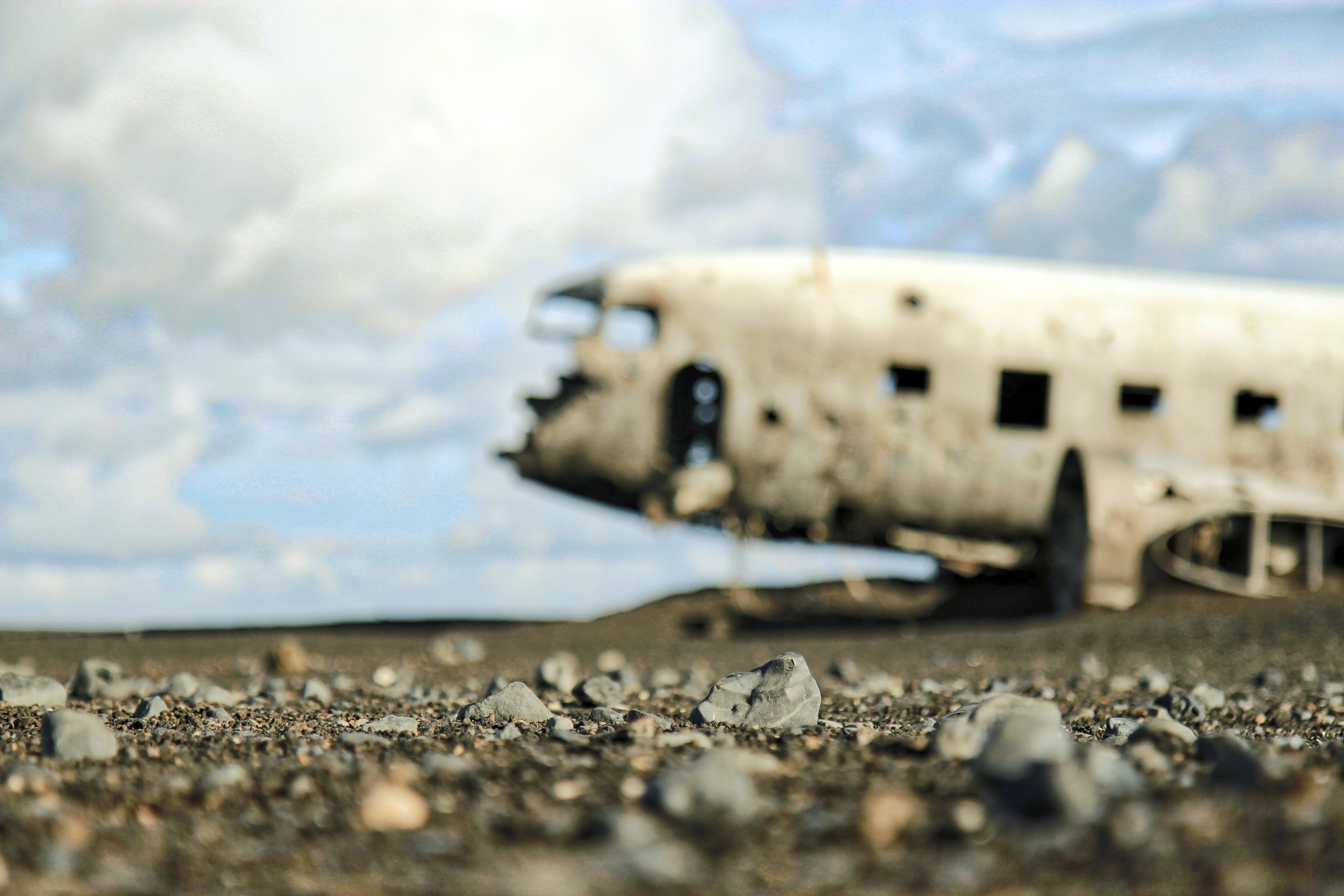 Macro view of pebbles with blurry plane wreckage and cloudy sky in the background