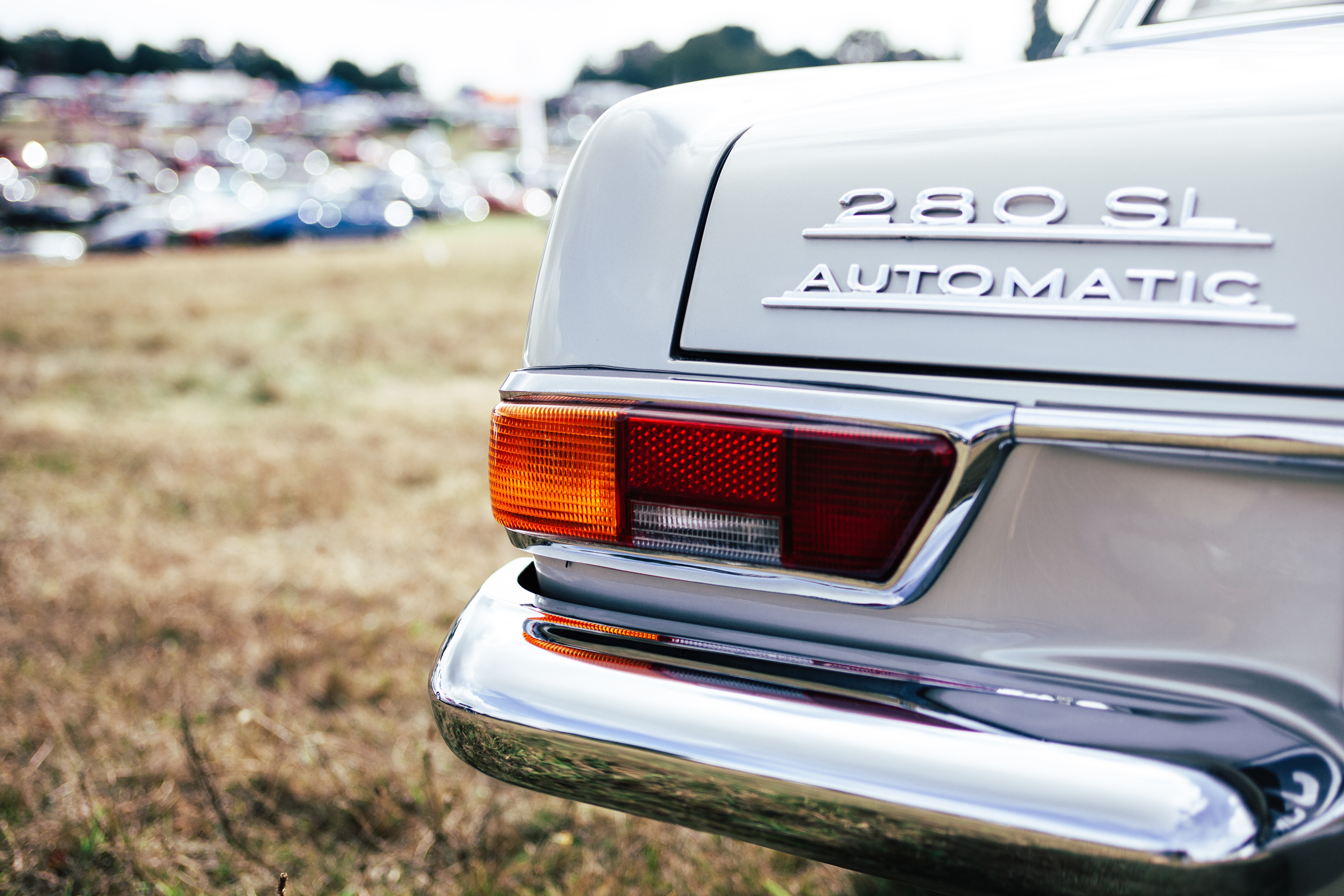 Macro of classic car with tail lights with 280 SL Automatic decals on trunk