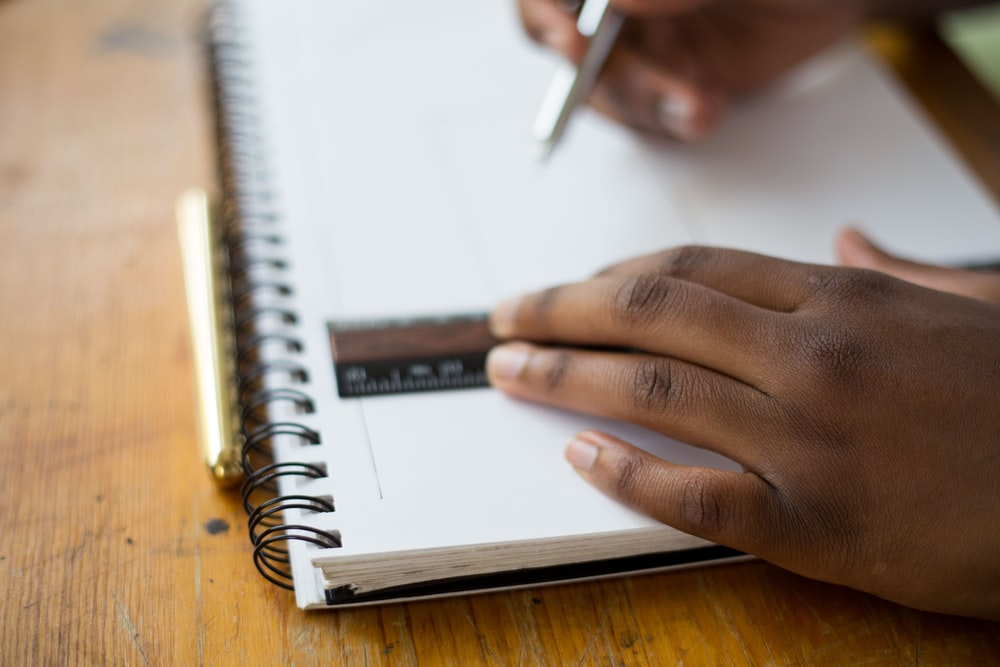 person holding ruler and pencil on spiral notebook