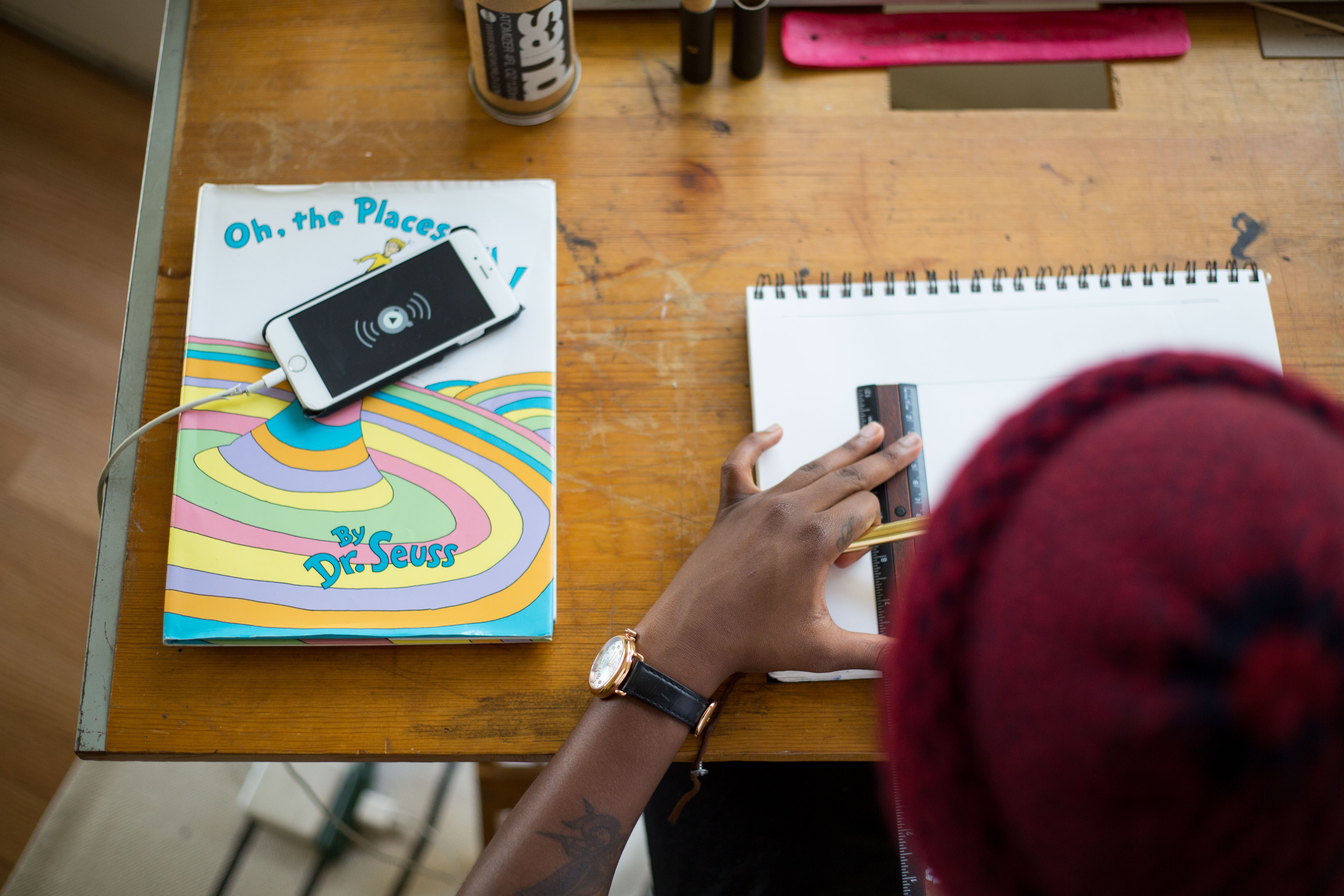 A person in a beanie drawing in a sketchbook with a ruler on a desk with a Dr. Seuss book on the side