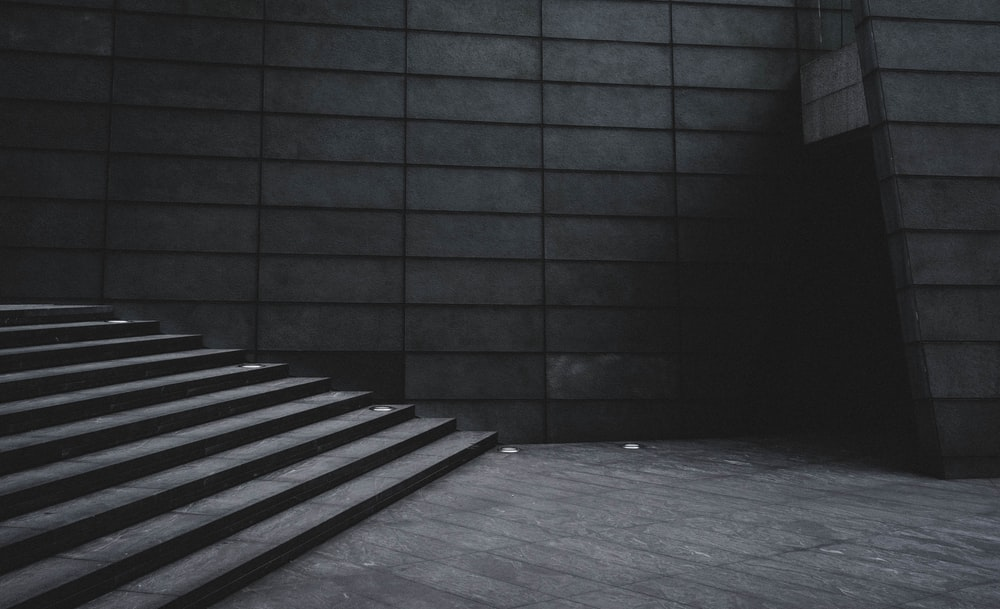 grayscale photo of stairs beside building