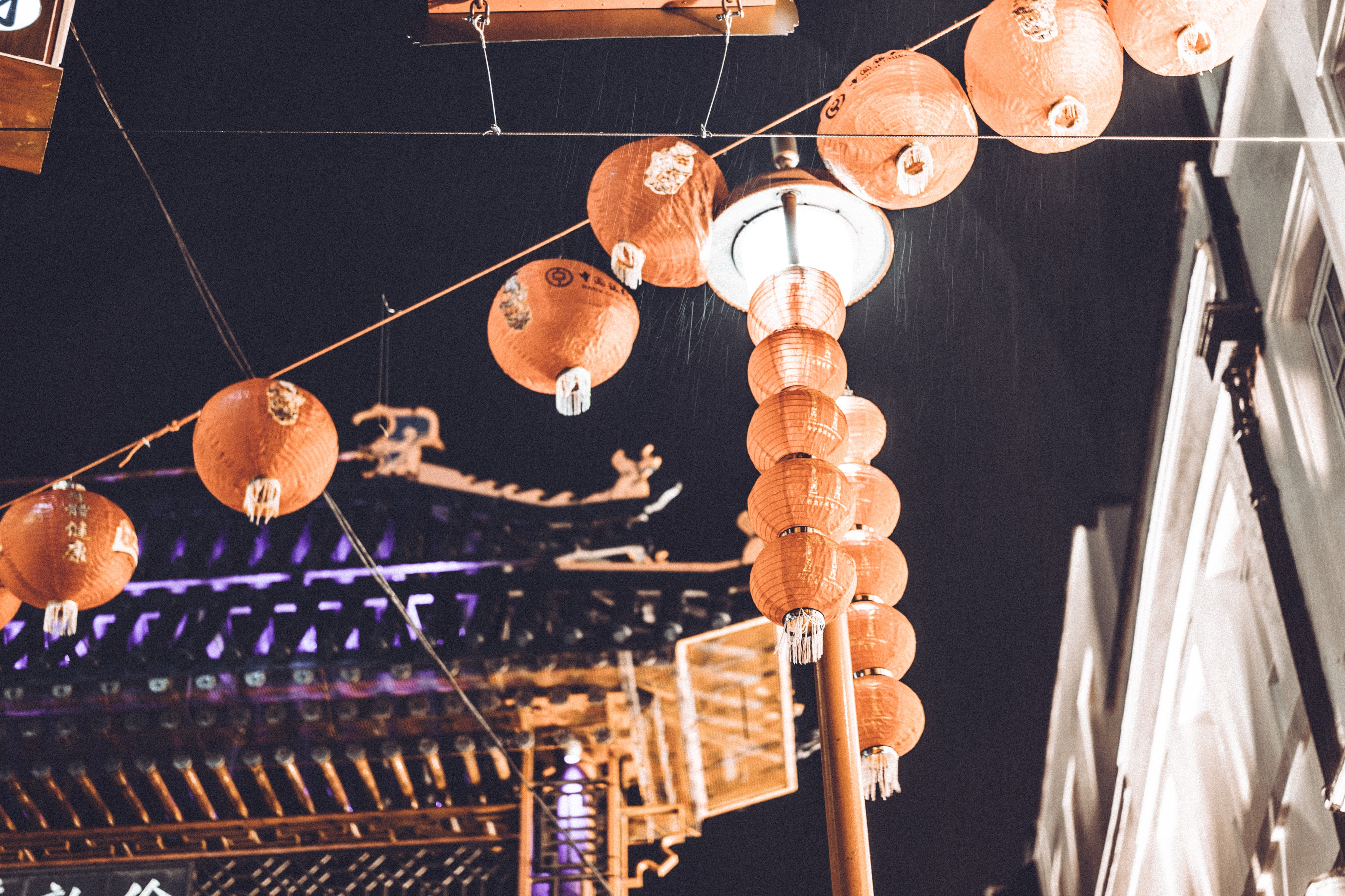 Strings of paper lanterns aside a lit up pagoda in Chinatown London Market