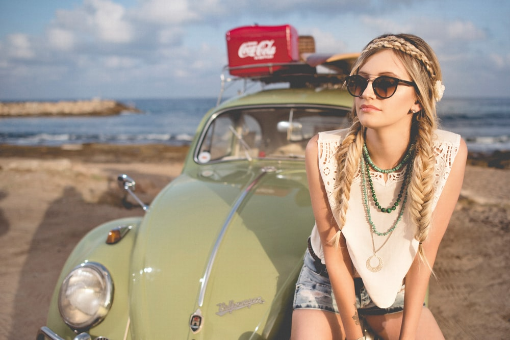 selective focus photography of woman sitting on Volkswagen Beetle parked on beach shore