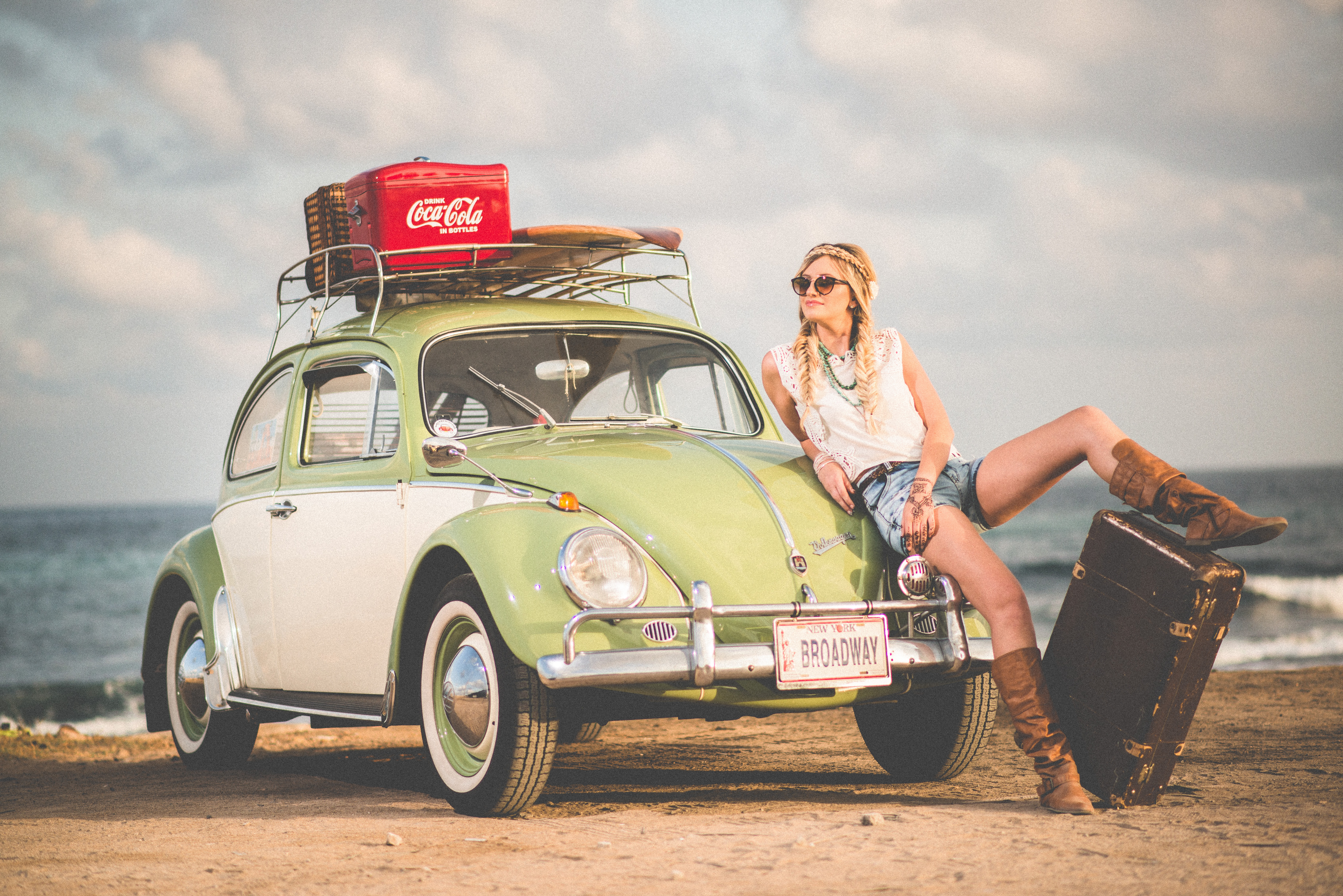 Bohemian woman with braided hair, sunglass, and a luggage sitting on top of a vintage volkswagen with a coca cola case on the beach.