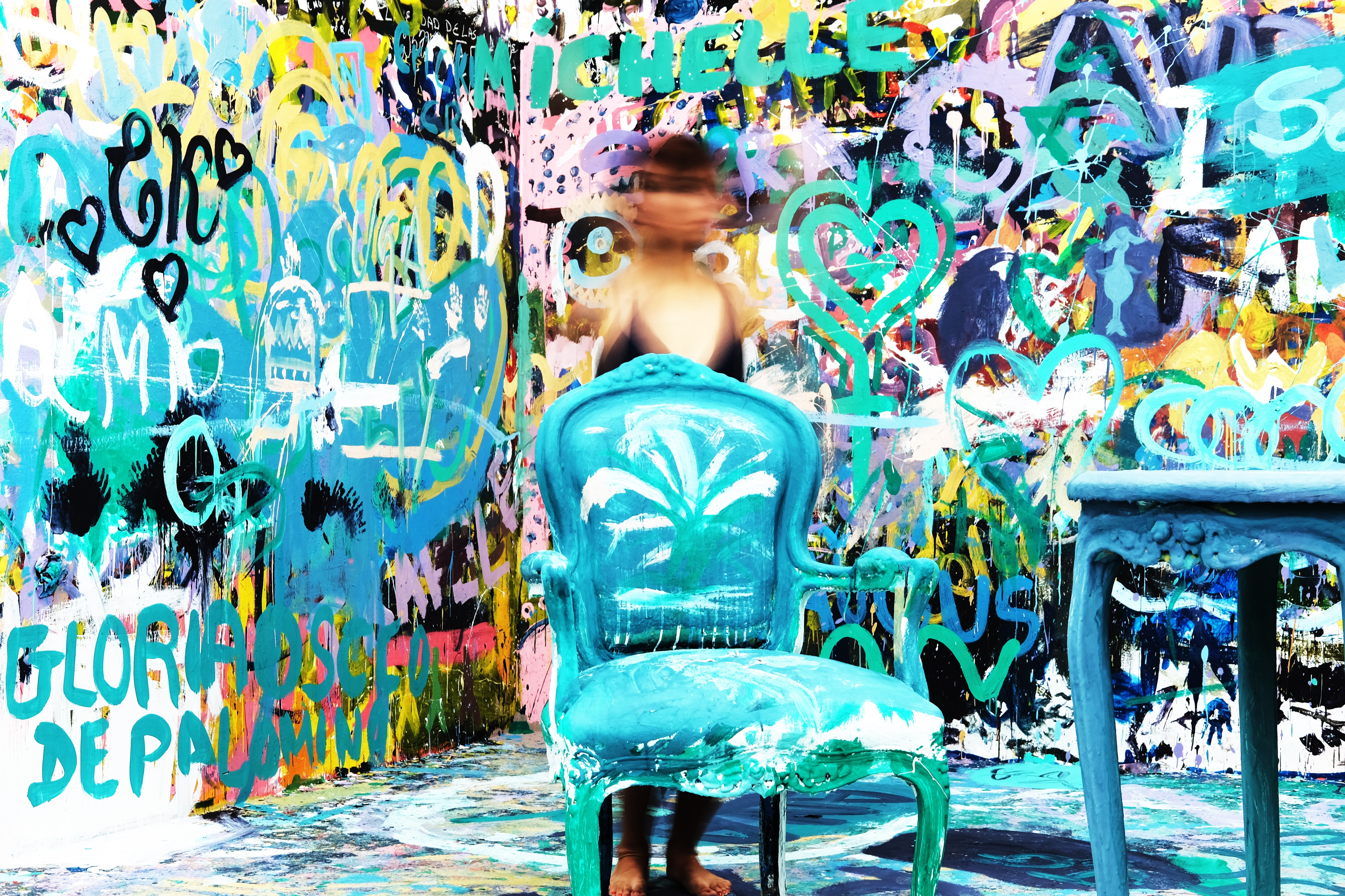Aqua coloured chair and table in room with wall covered in graffiti, MATE Museo Mario Testino