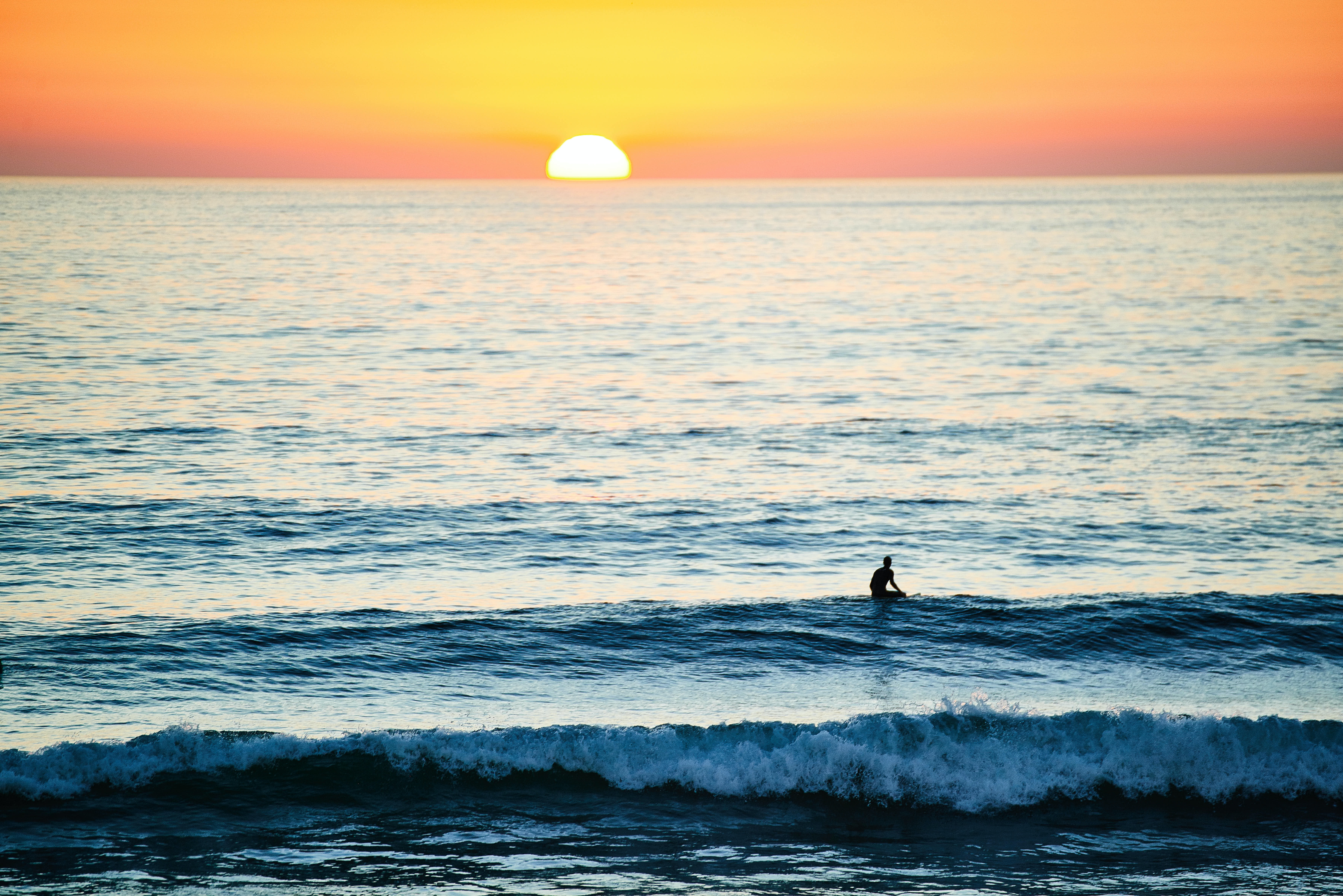 A solitary surfer in the waves at Hossegor, as the sun sets on the horizon leaving an orange sky