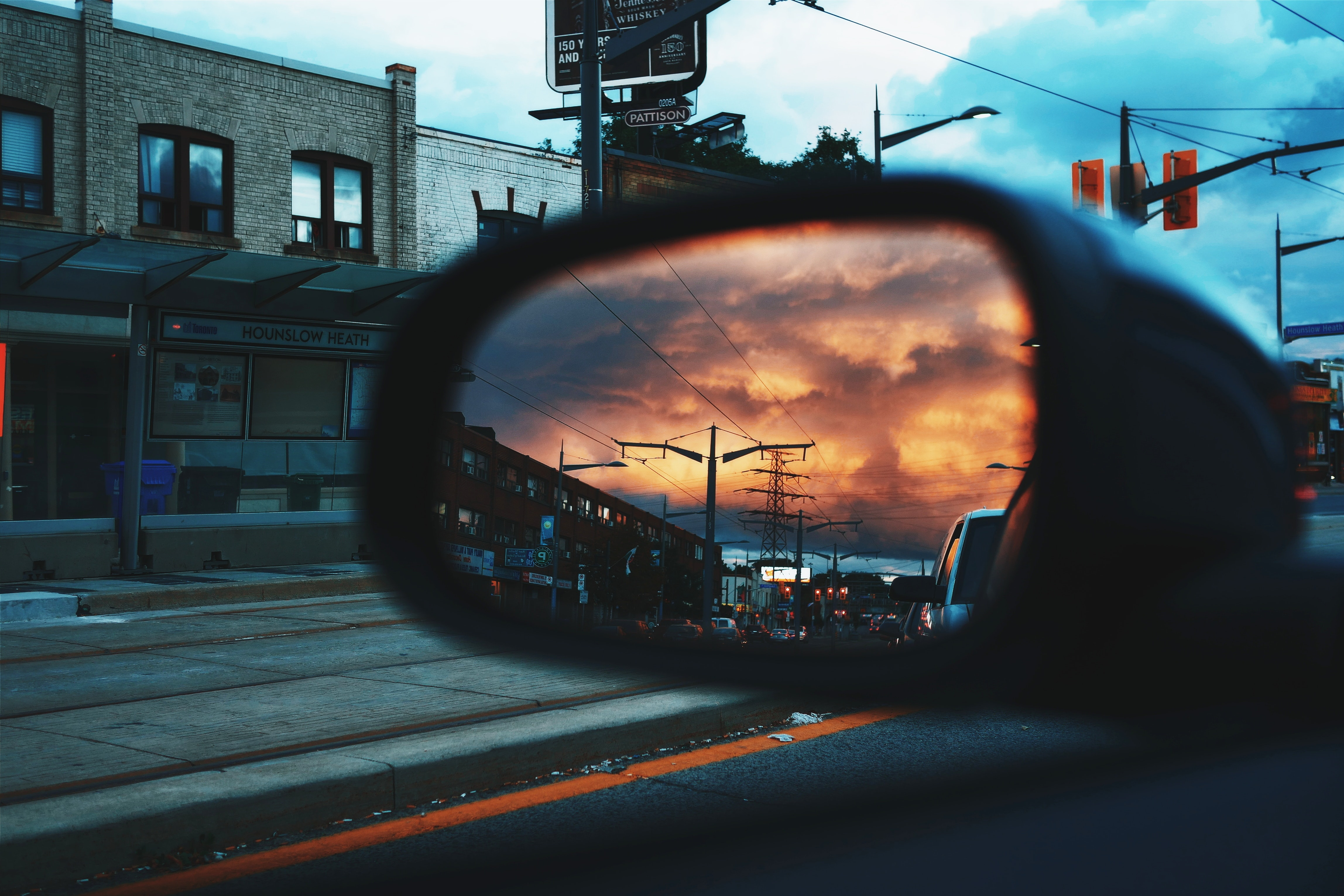 The view of an orange sky and the road from a side mirror on a car in Toronto