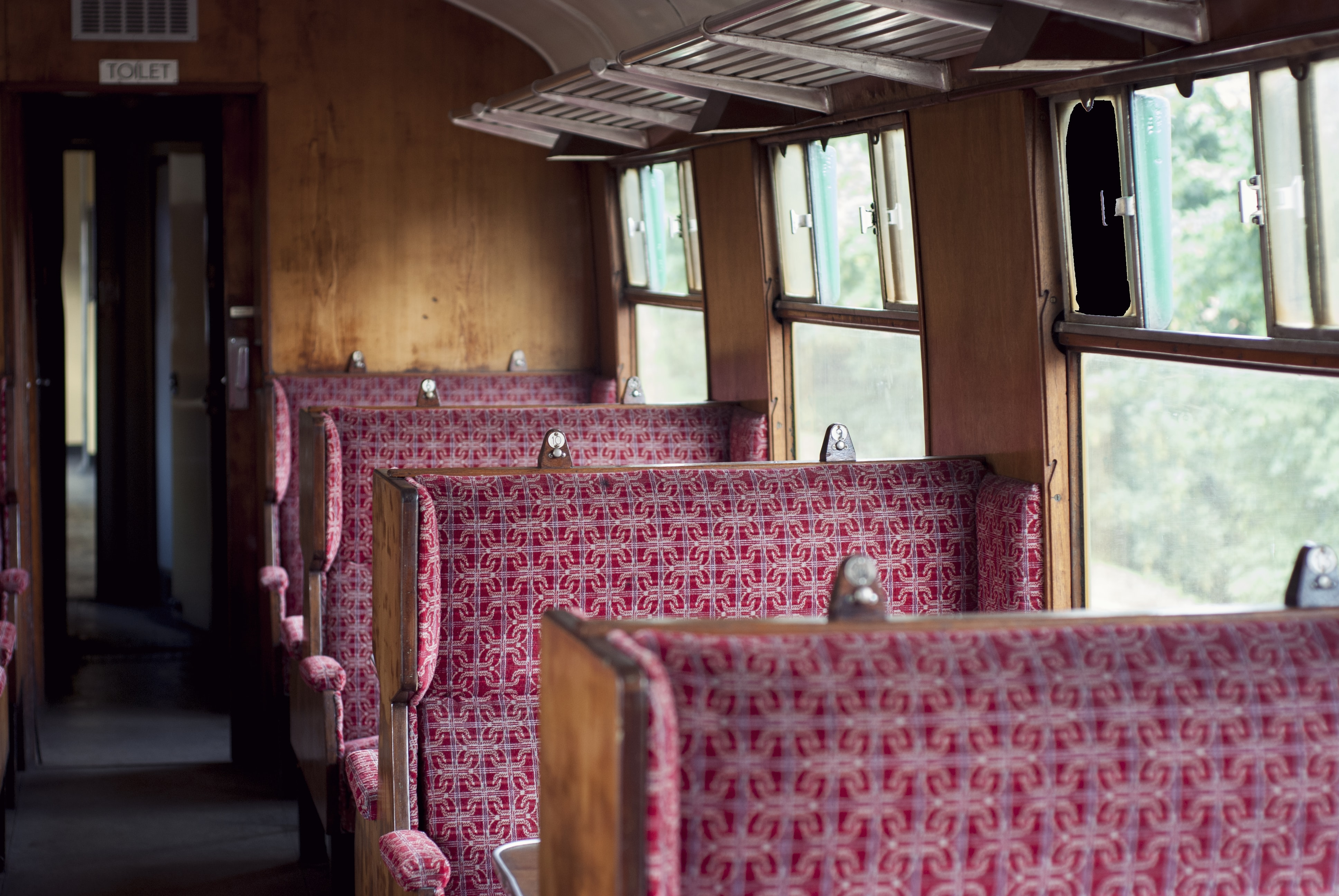 Interior of the old vintage British railway passenger carriage with wooden benches in Ropley