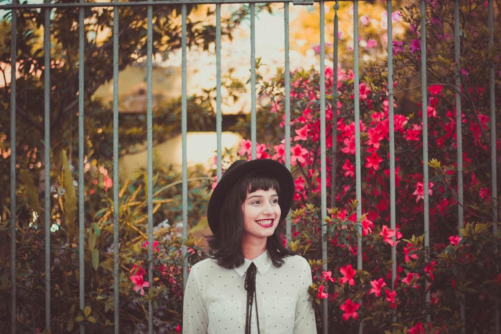 women's white dress shirt standing gray fence