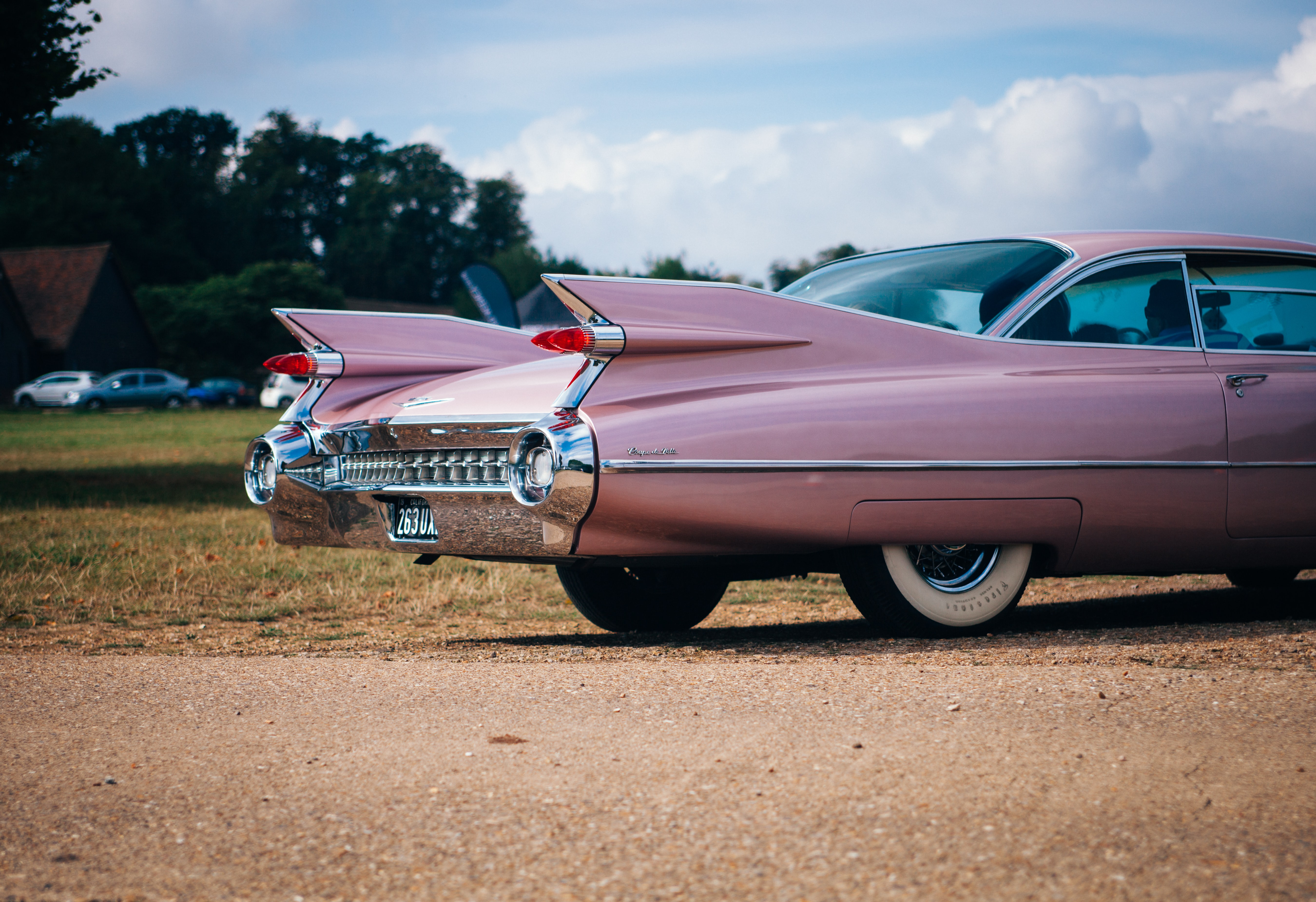 vintage pink muscle car parked near field of grass