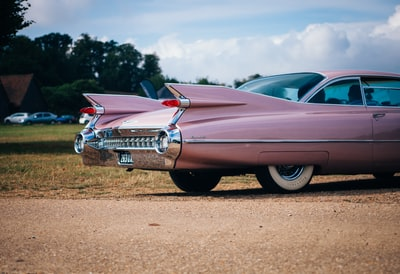 vintage pink muscle car parked near field of grass classic car teams background