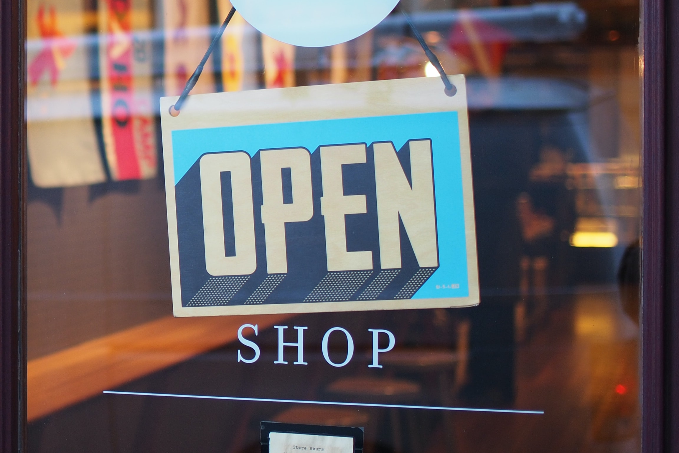 """An """"open"""" sign hanging on a store door"""