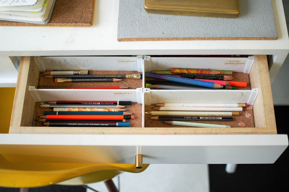 colored pencils in white wooden drawer