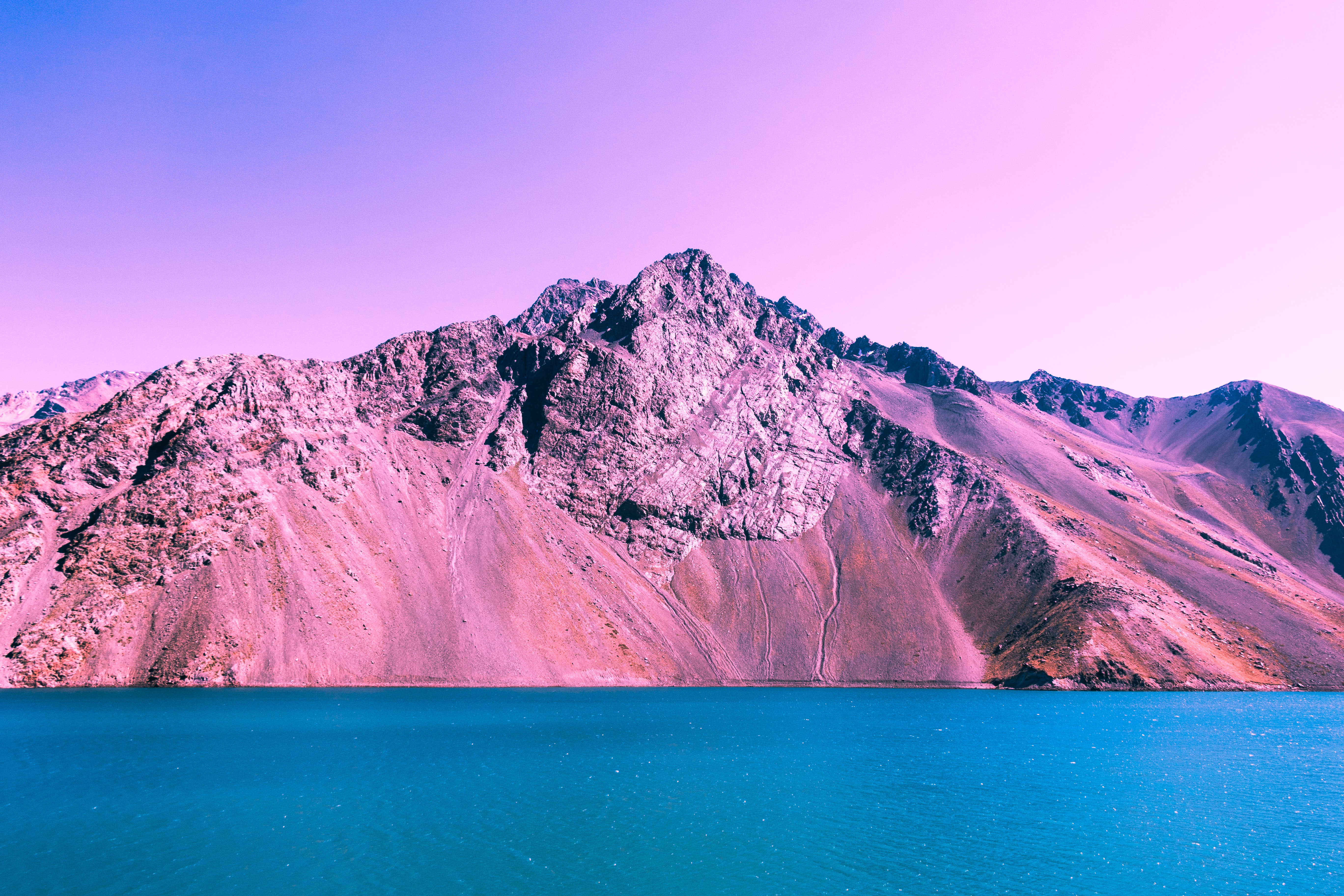 Pink and purple mountain ridge by a blue lake