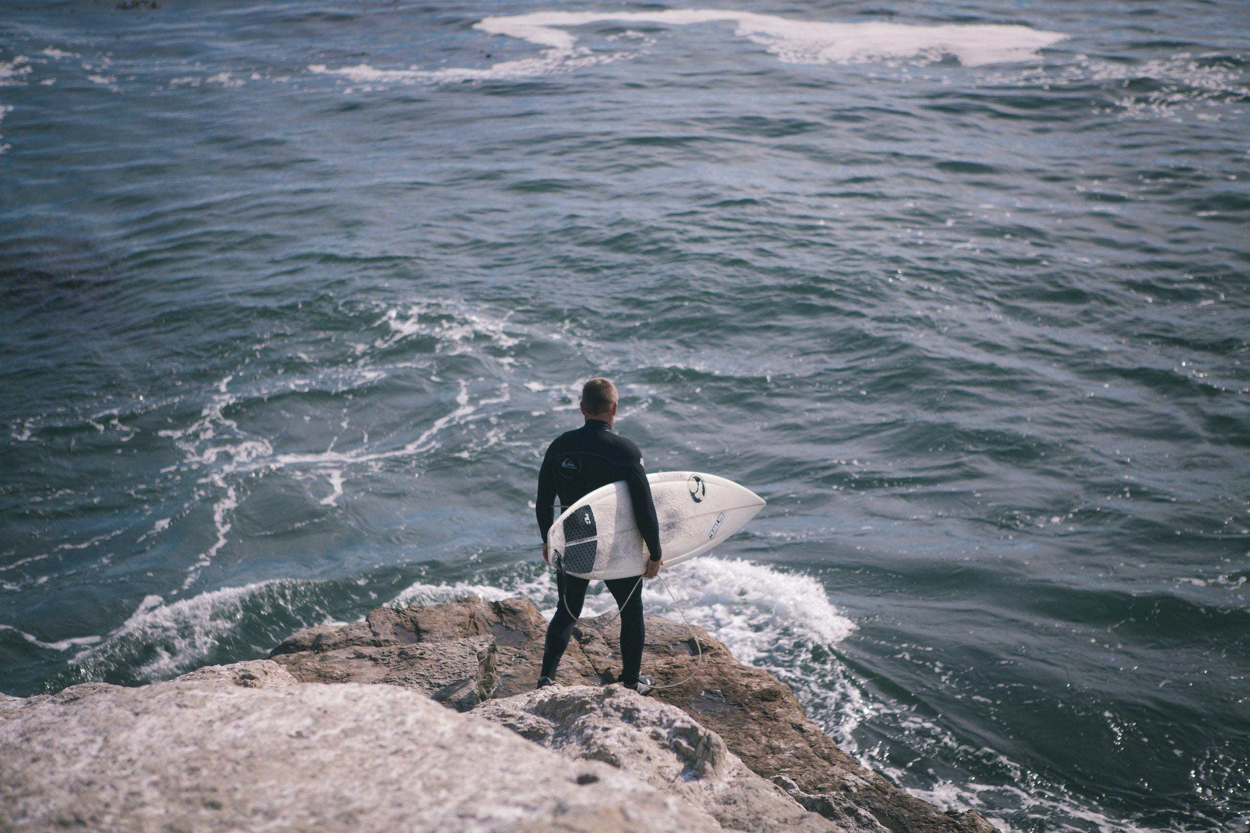 A man holding a surfboard on a rock by the ocean in Santa Cruz