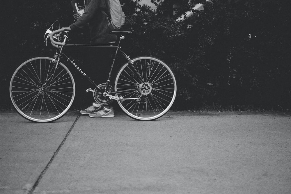 grayscale photo of person holding a bicycle