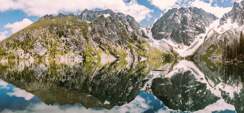 rocky mountains covered with green grass reflected on body of water under white and blue cloudy sky