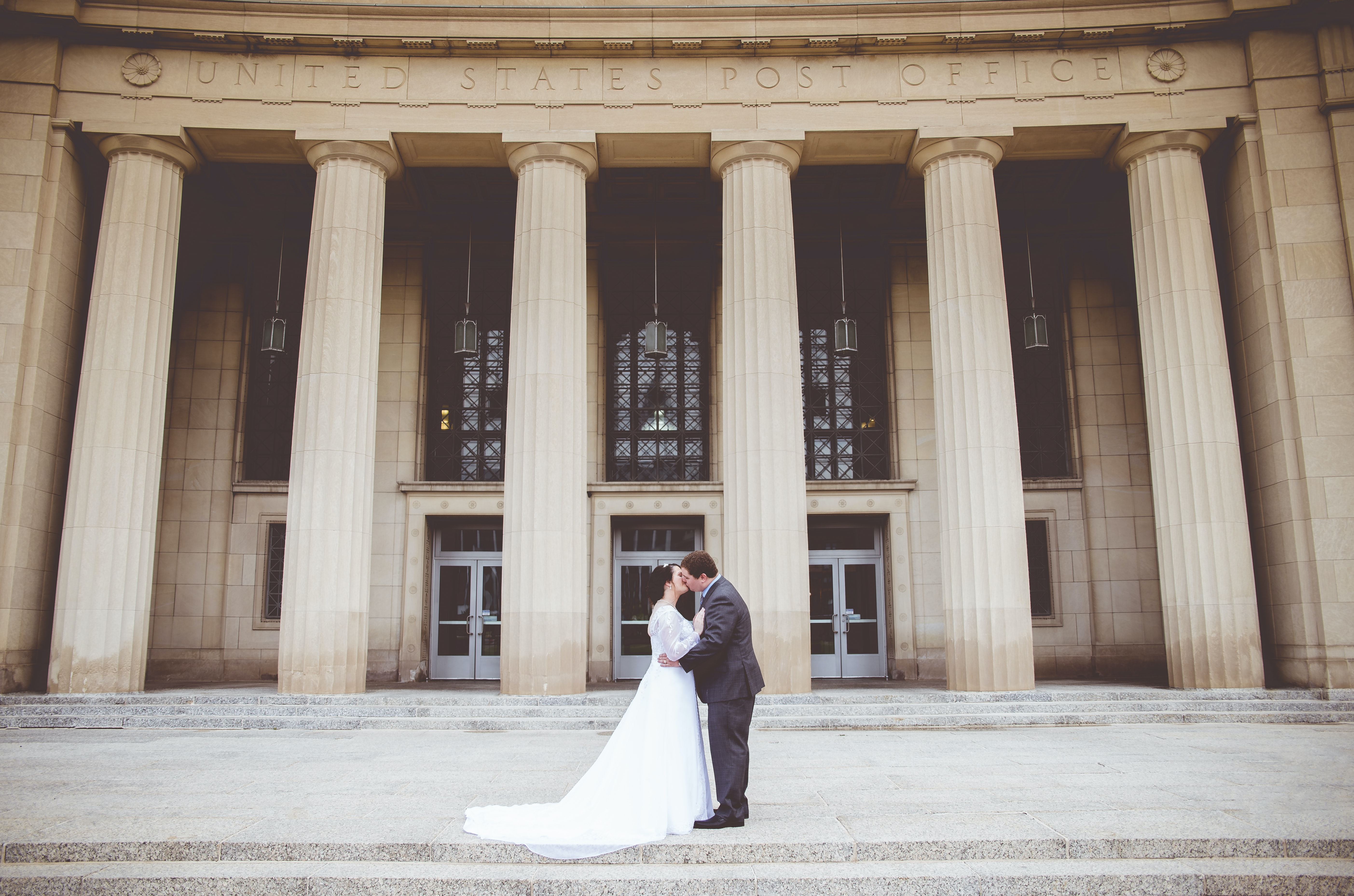 A married couple kisses in front of a US Post Office building with tall columns
