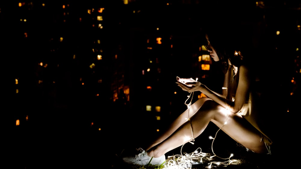 woman in white sneakers using smartphone