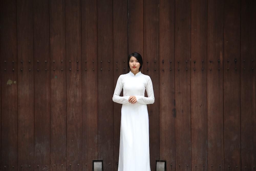 woman standing near brown wall