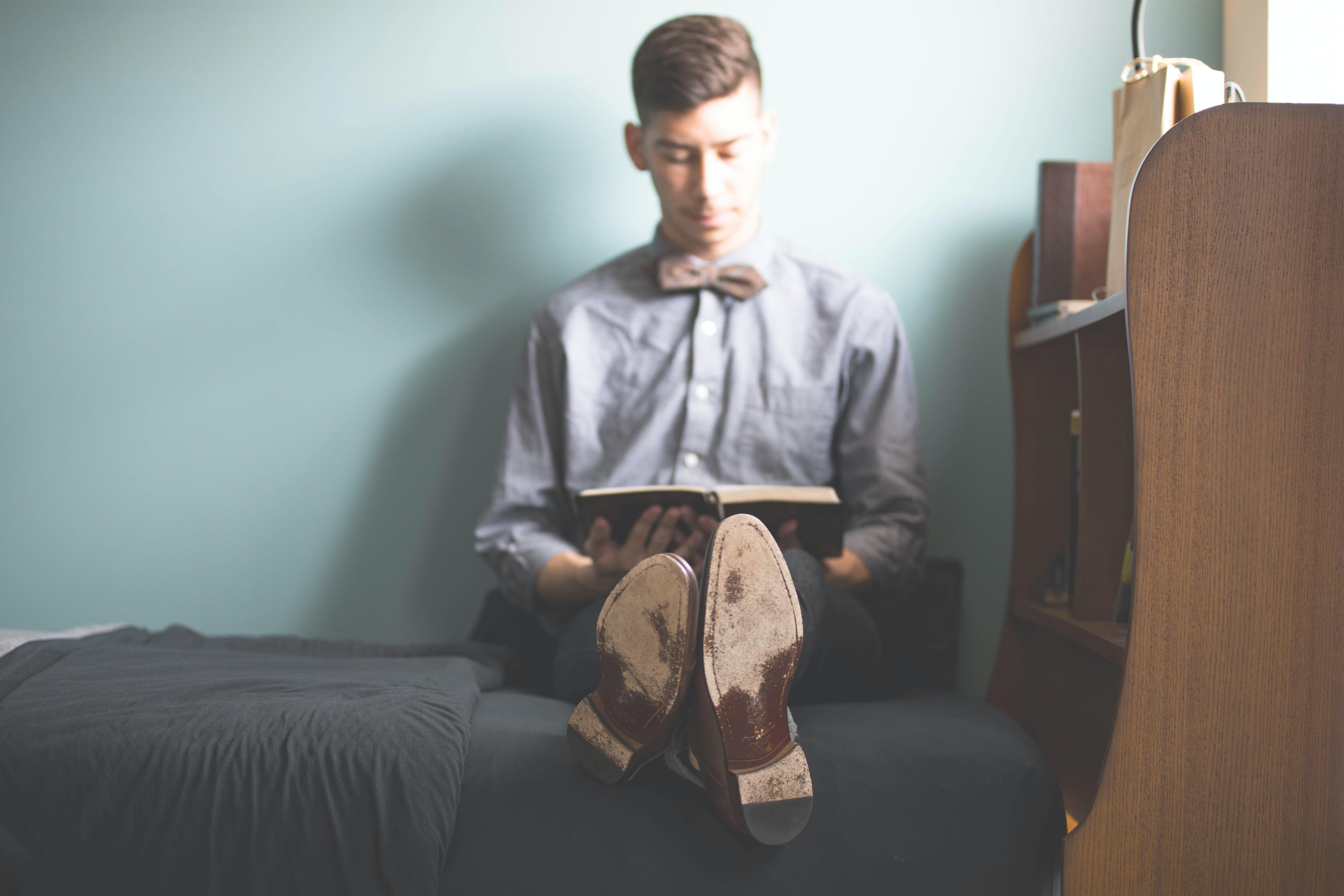 man wearing gray dress shirt reading book