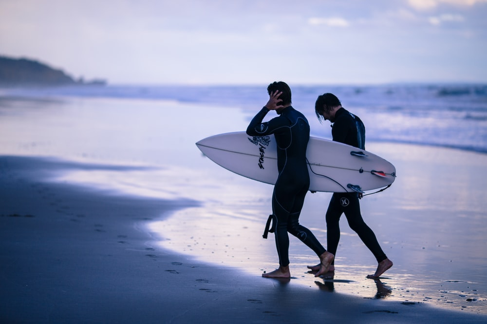 person walking on seashore holding surfboard