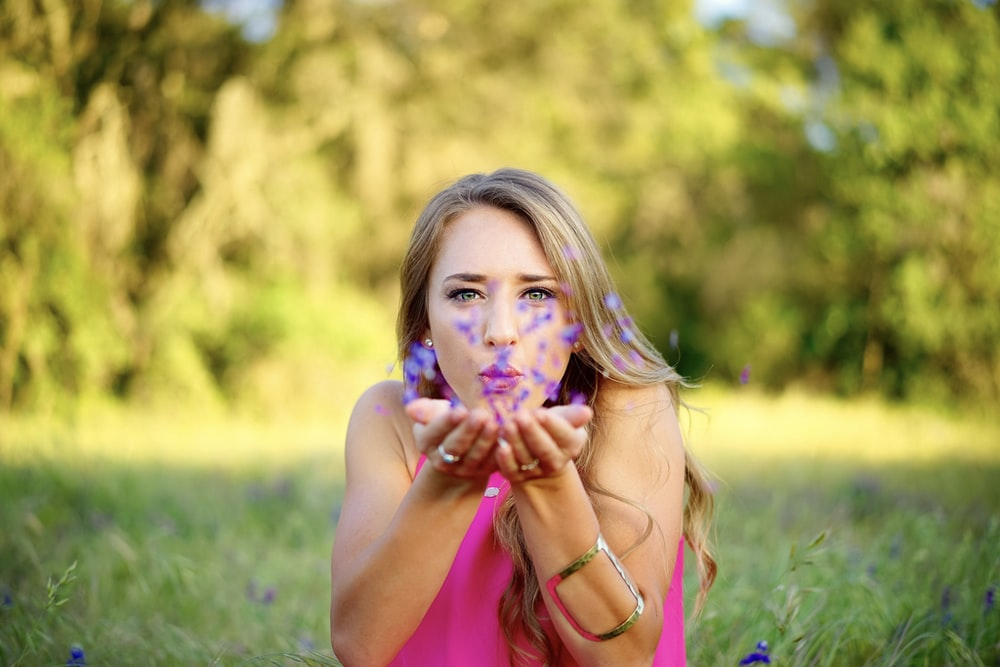 woman wearing pink sleeveless top blowing purple flowers