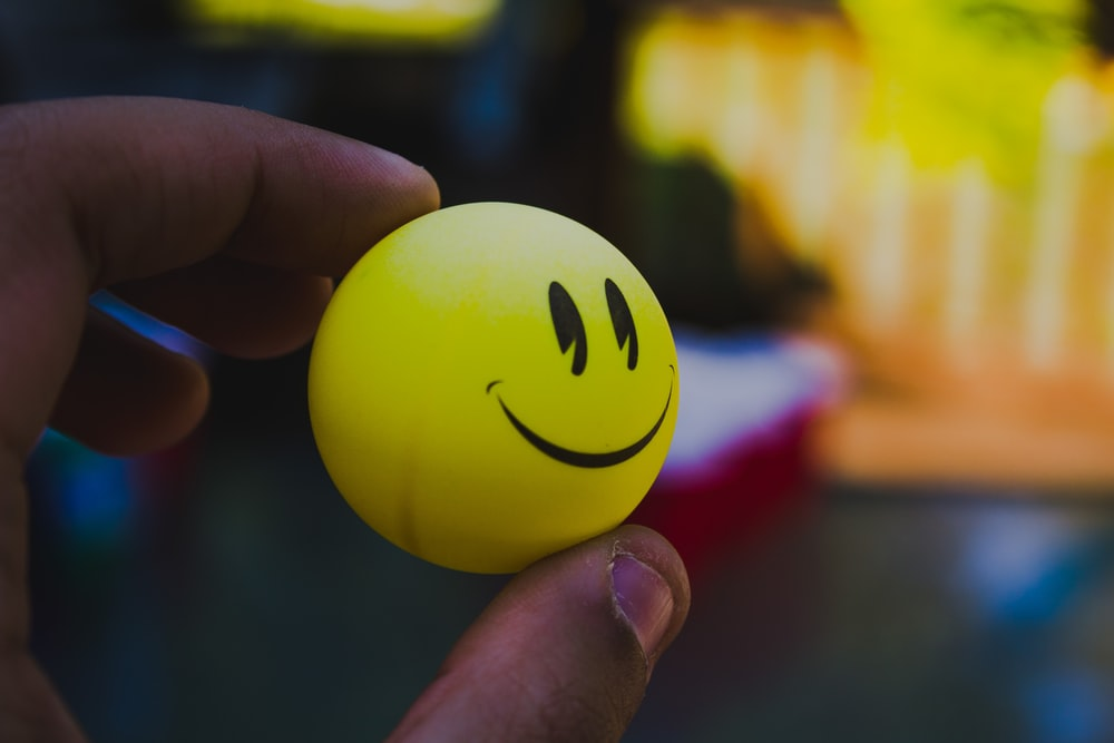 person holding yellow emoji ball