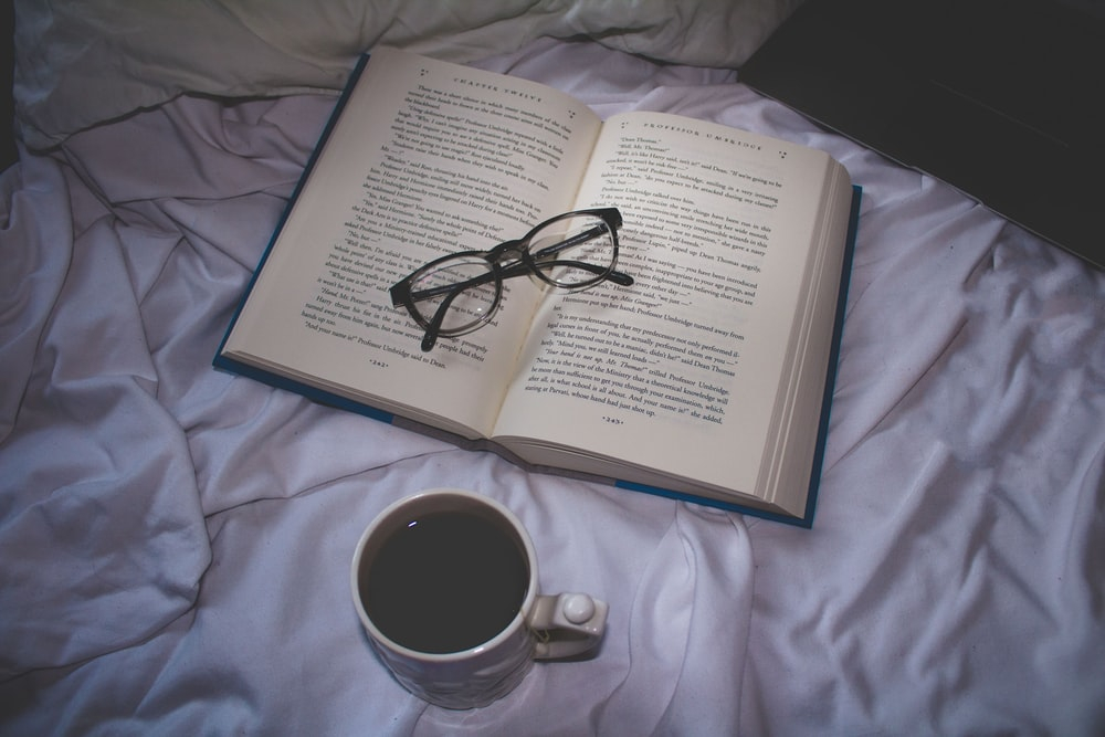 cup of coffee near open book with eyeglasses