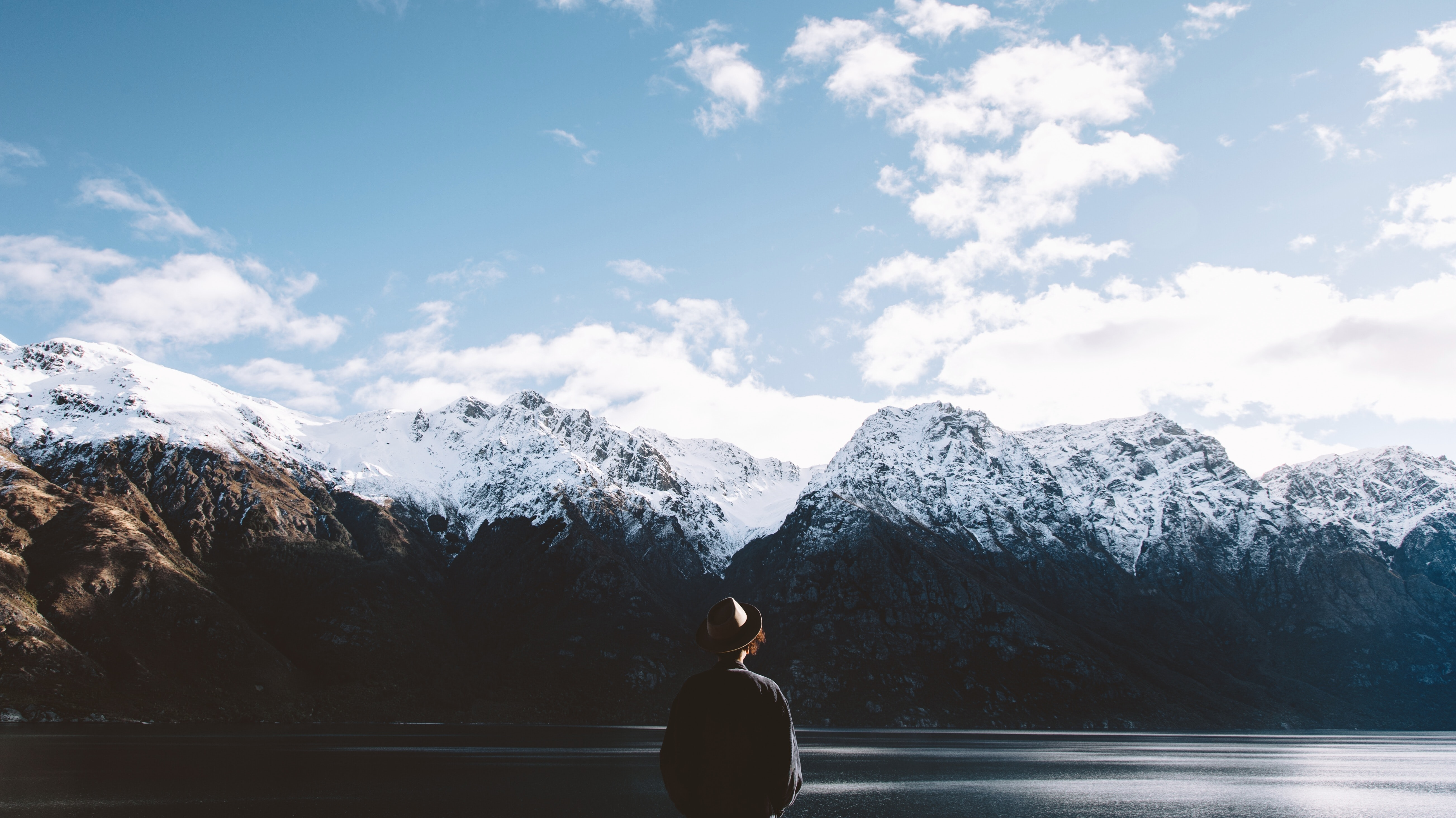 A person in a hat standing on the shore of a lake surrounded by snow-topped mountain ridges