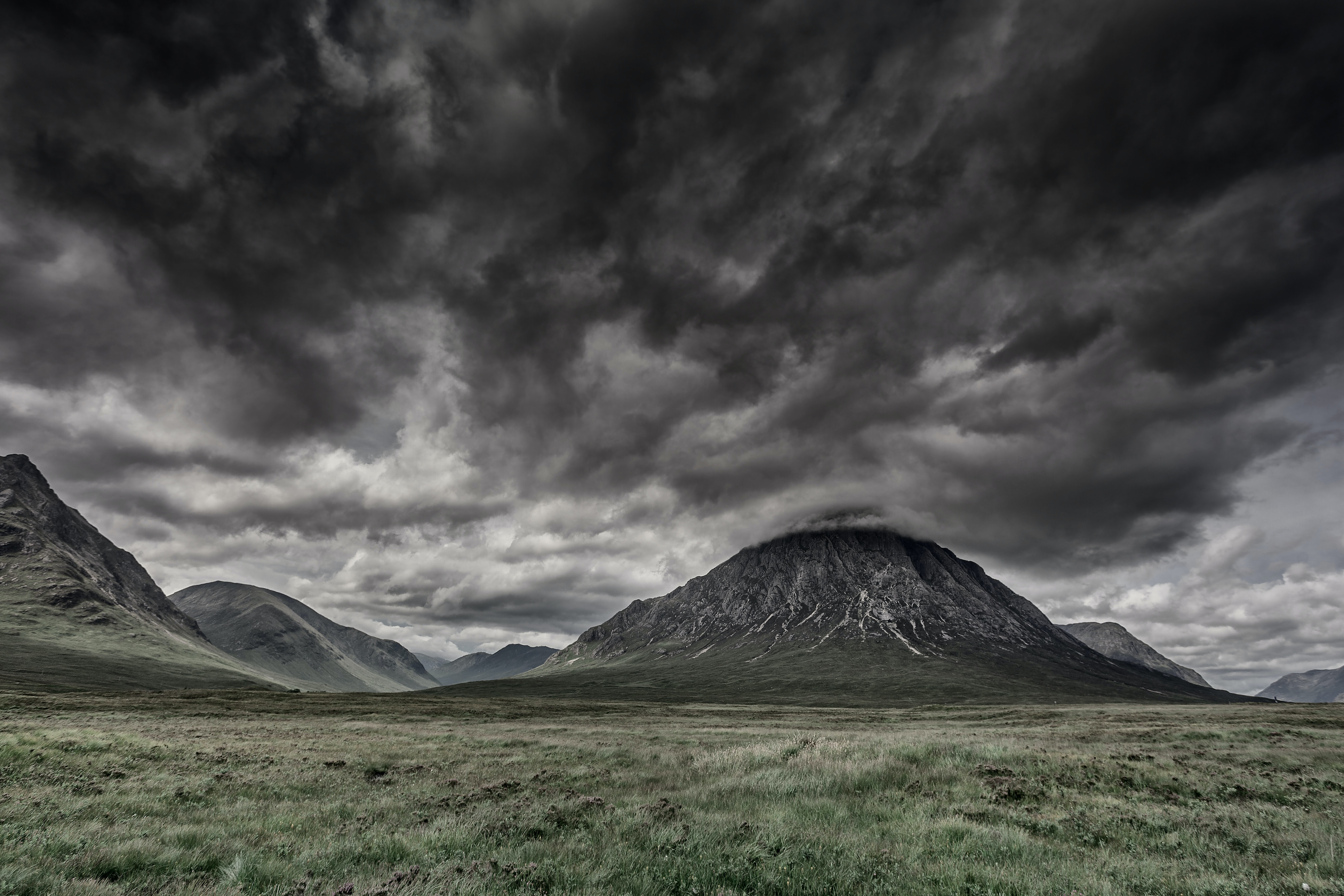 Dark, storm clouds above the valley with small rocky hills at Glencoe