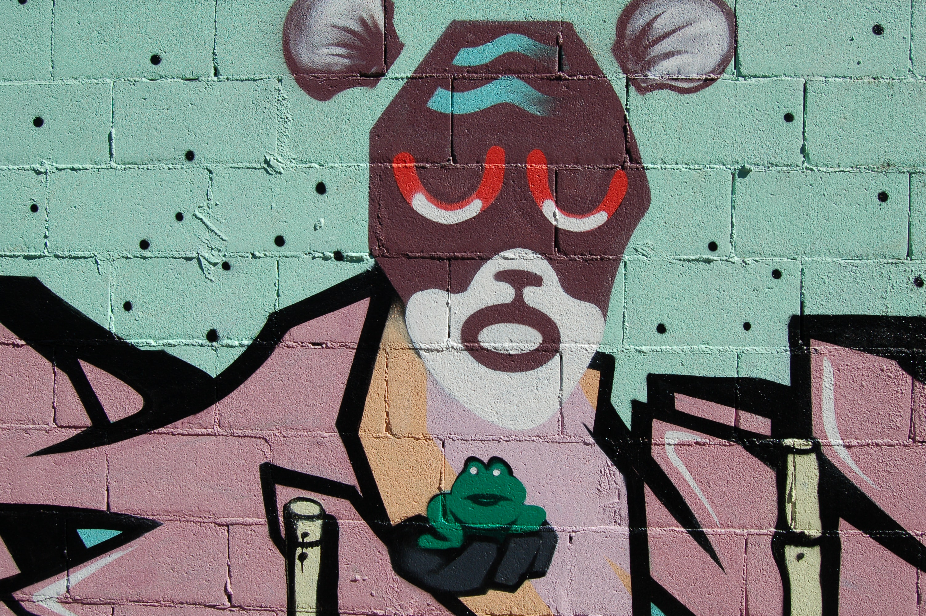 A weird face painted on a wall, holding a frog.