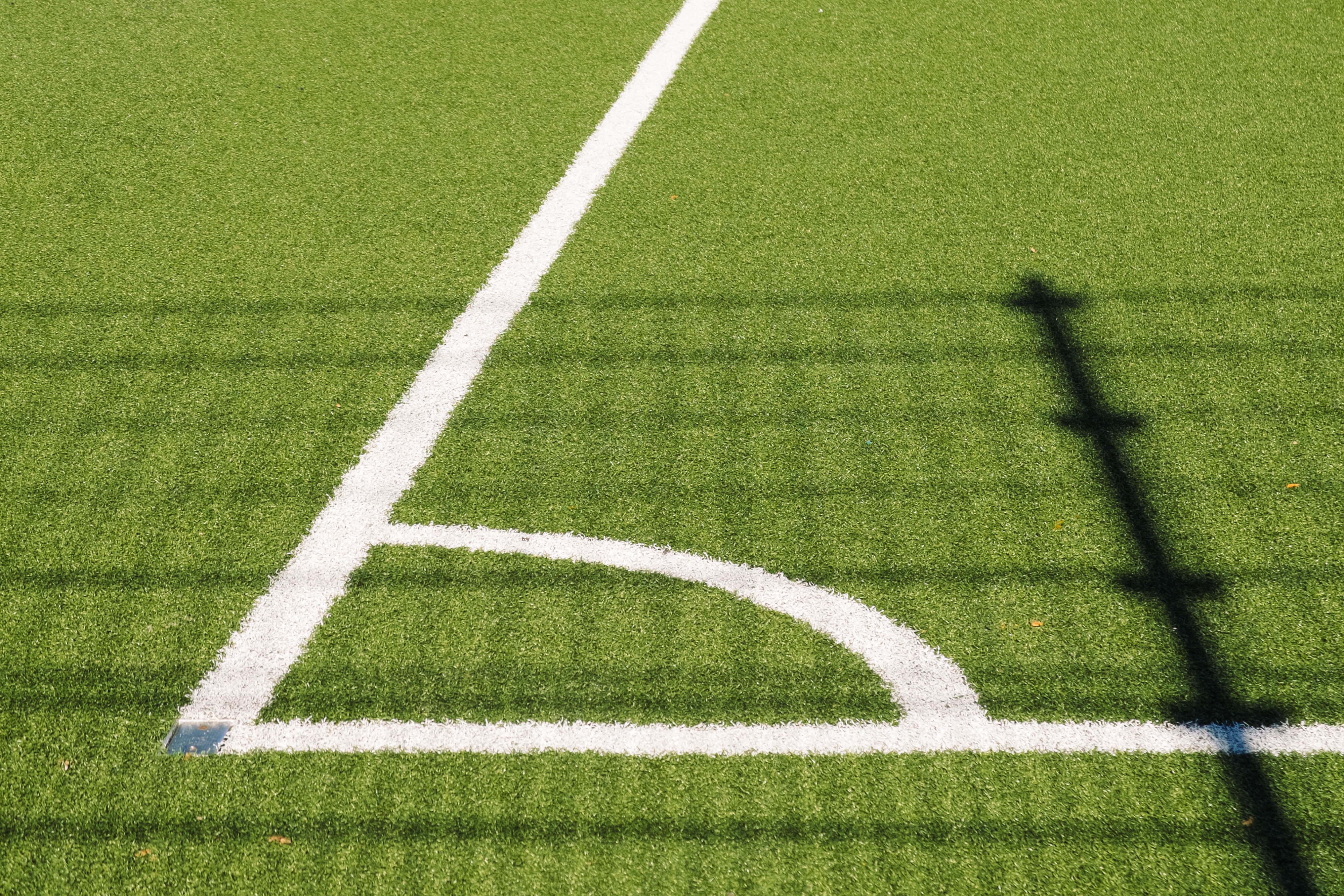 Corner of soccer field with white lines in an angle on turf