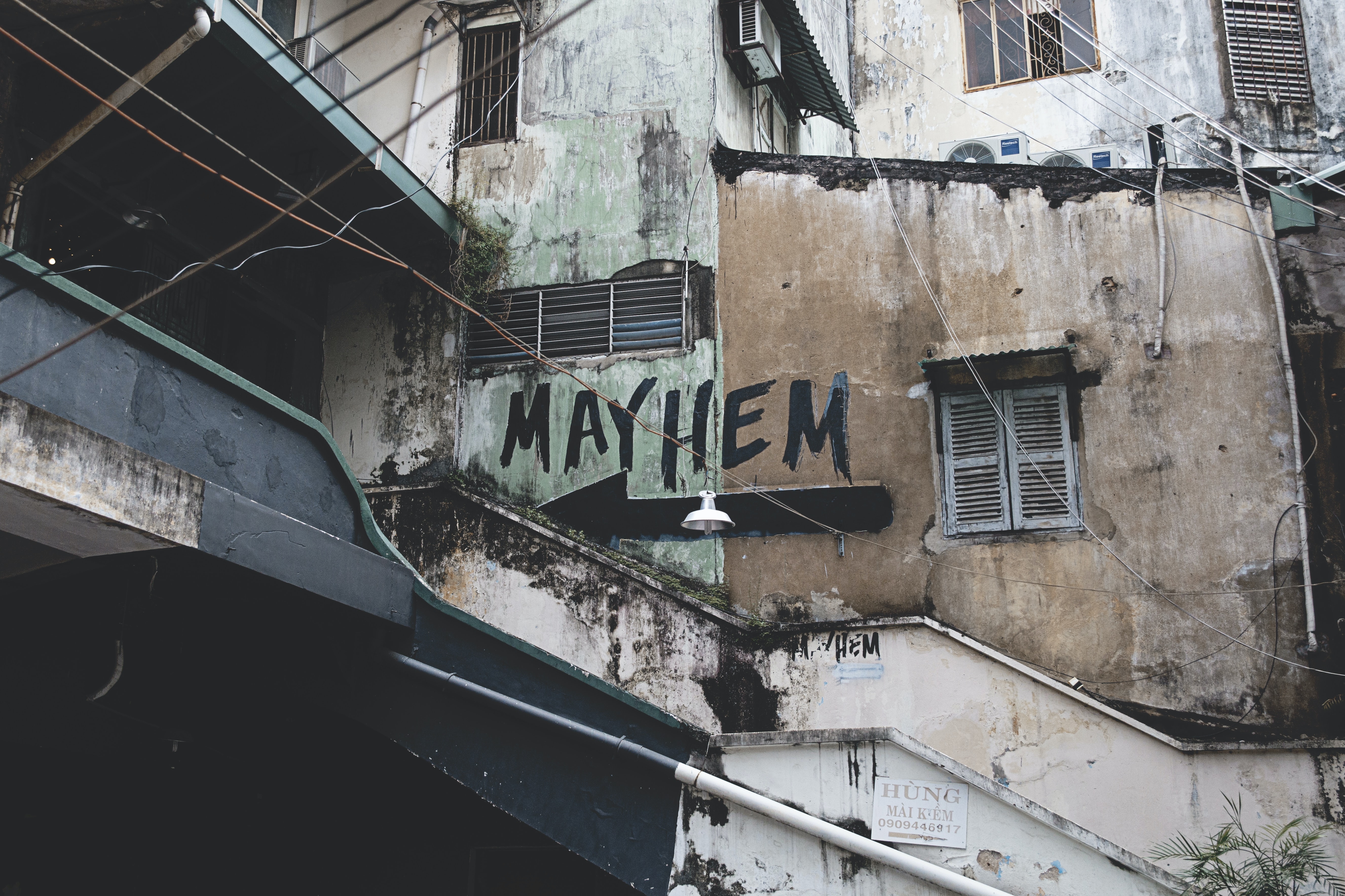 The exterior view of an urban building with an arrow and a mayhem text written on it in Ho Chi Minh City.