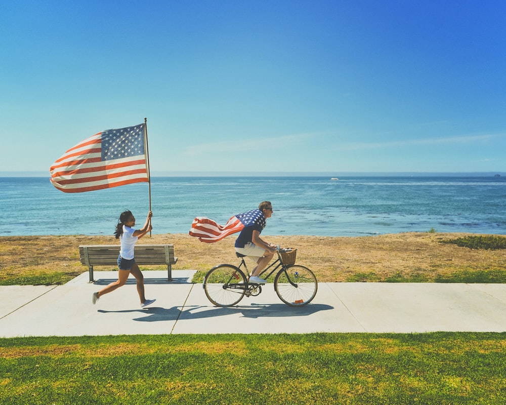 Man on a bicycle followed by a woman running with US flags at Shell Beach shoreline path