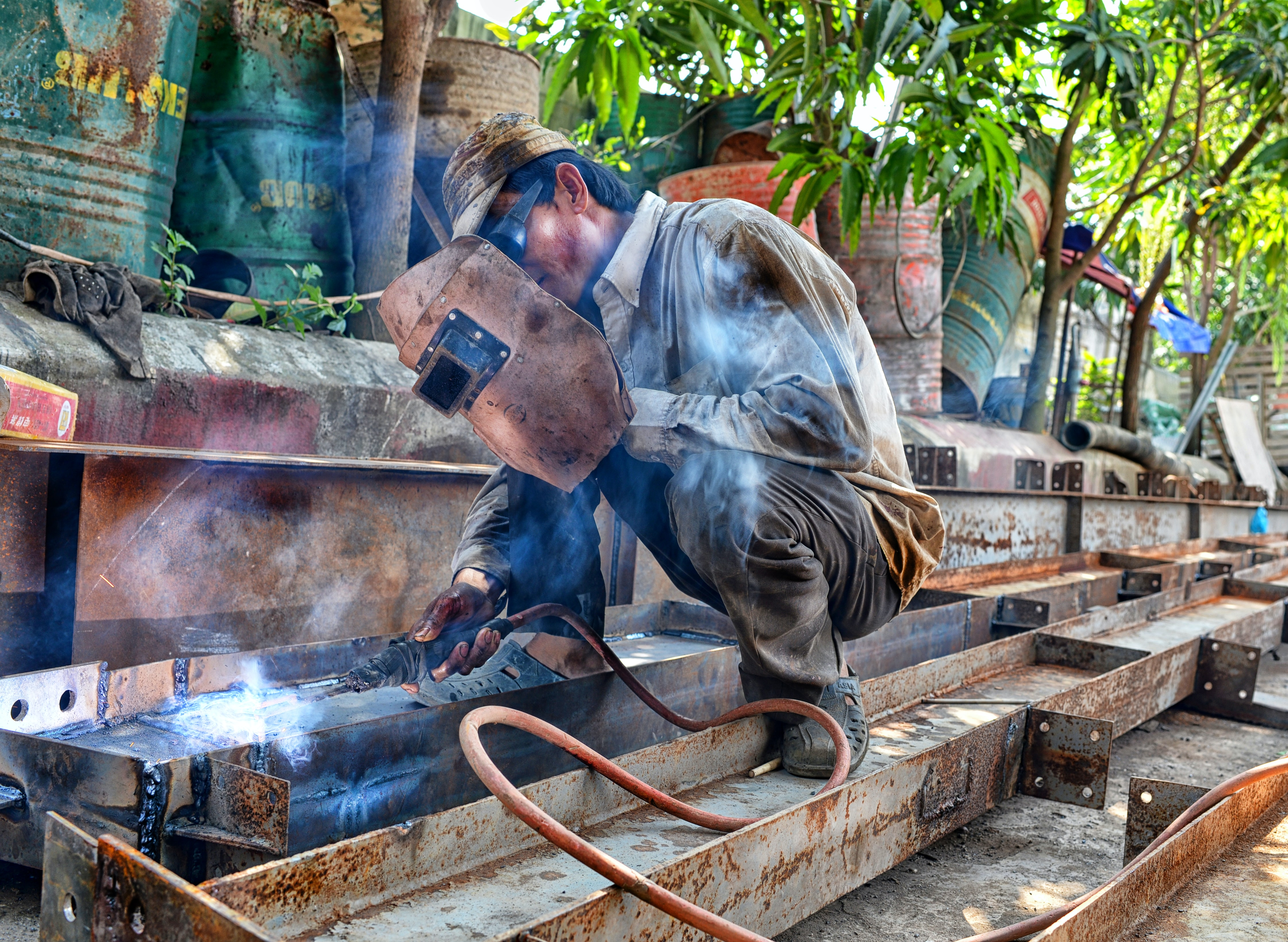 A crouching man with a welding helmet welding steel bars