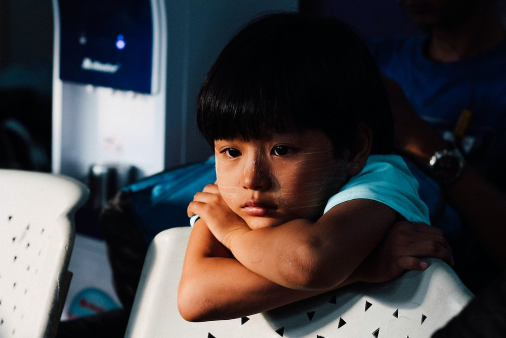 young boy leaning on white chair looking sad