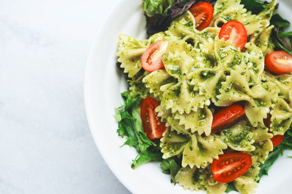 Pesto pasta with sliced tomatoes served on white ceramic plate