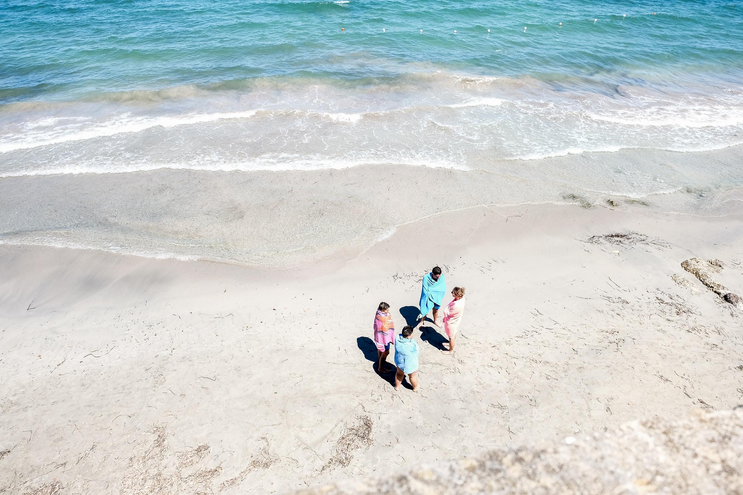 four people standing on seashore