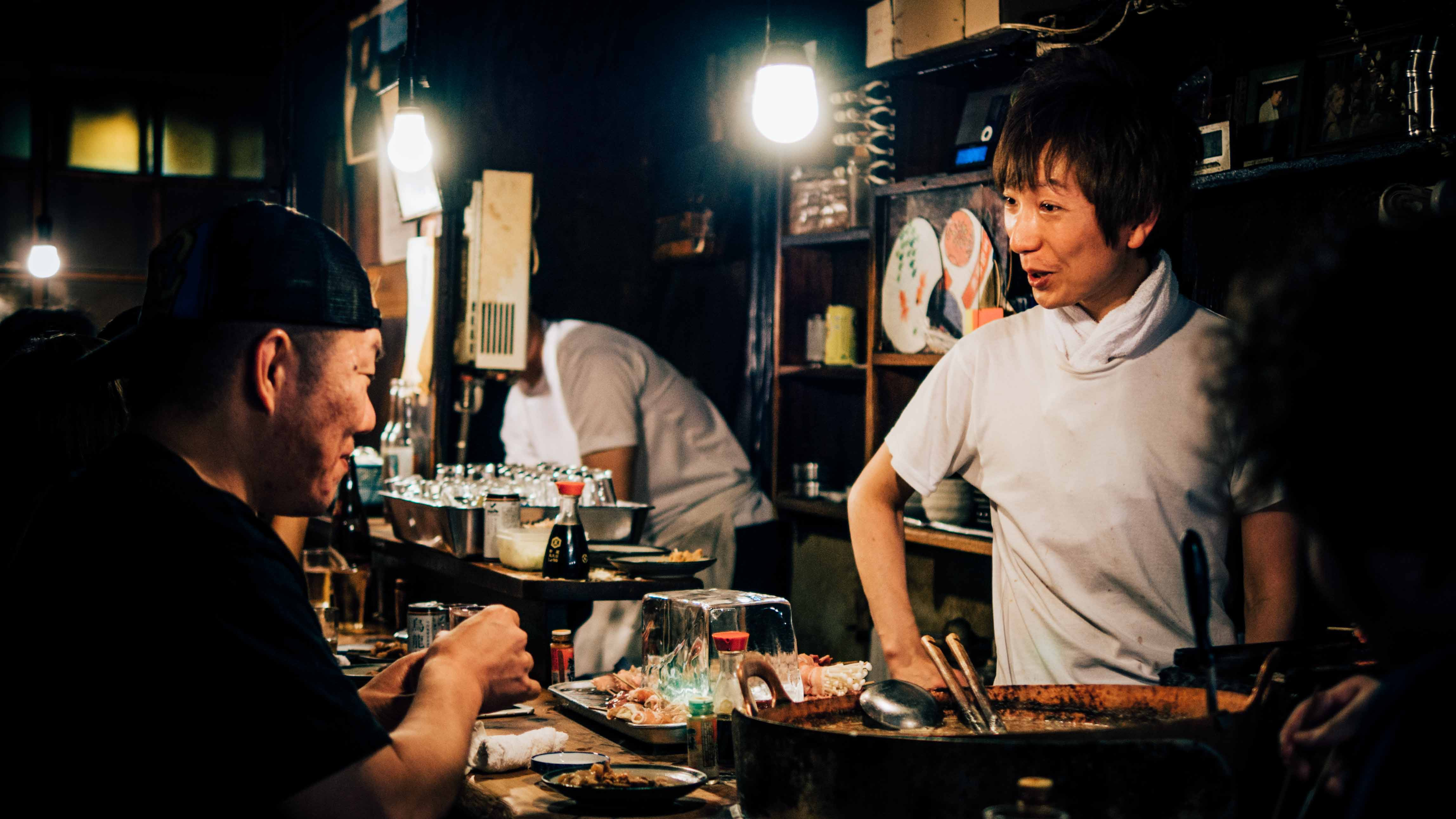 Waiter and patron talk over a meal at a restaurant in Japan