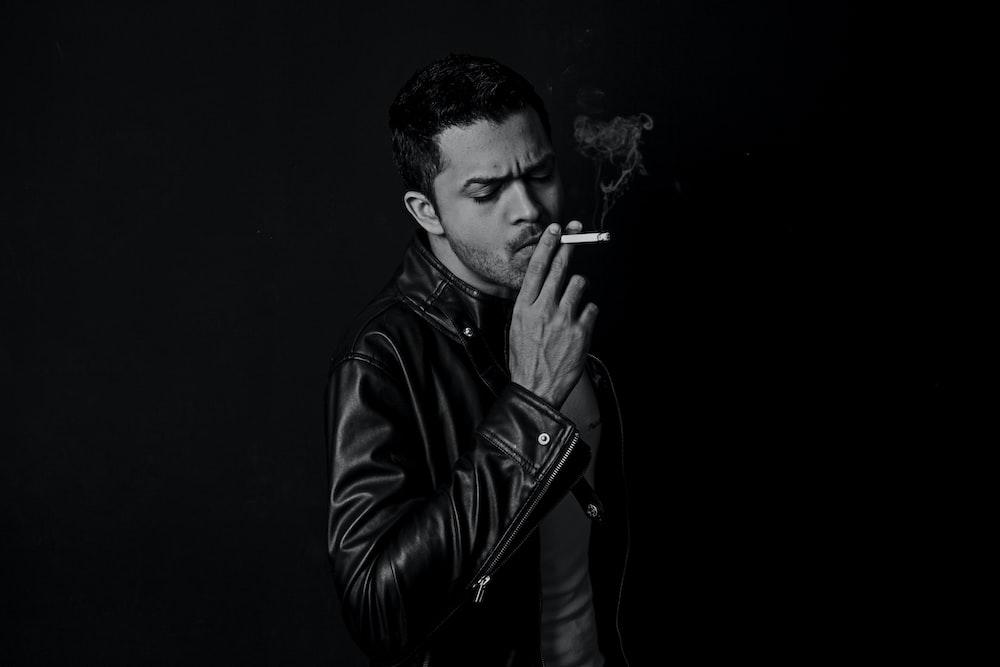 grayscale photo of man smoking cigarette