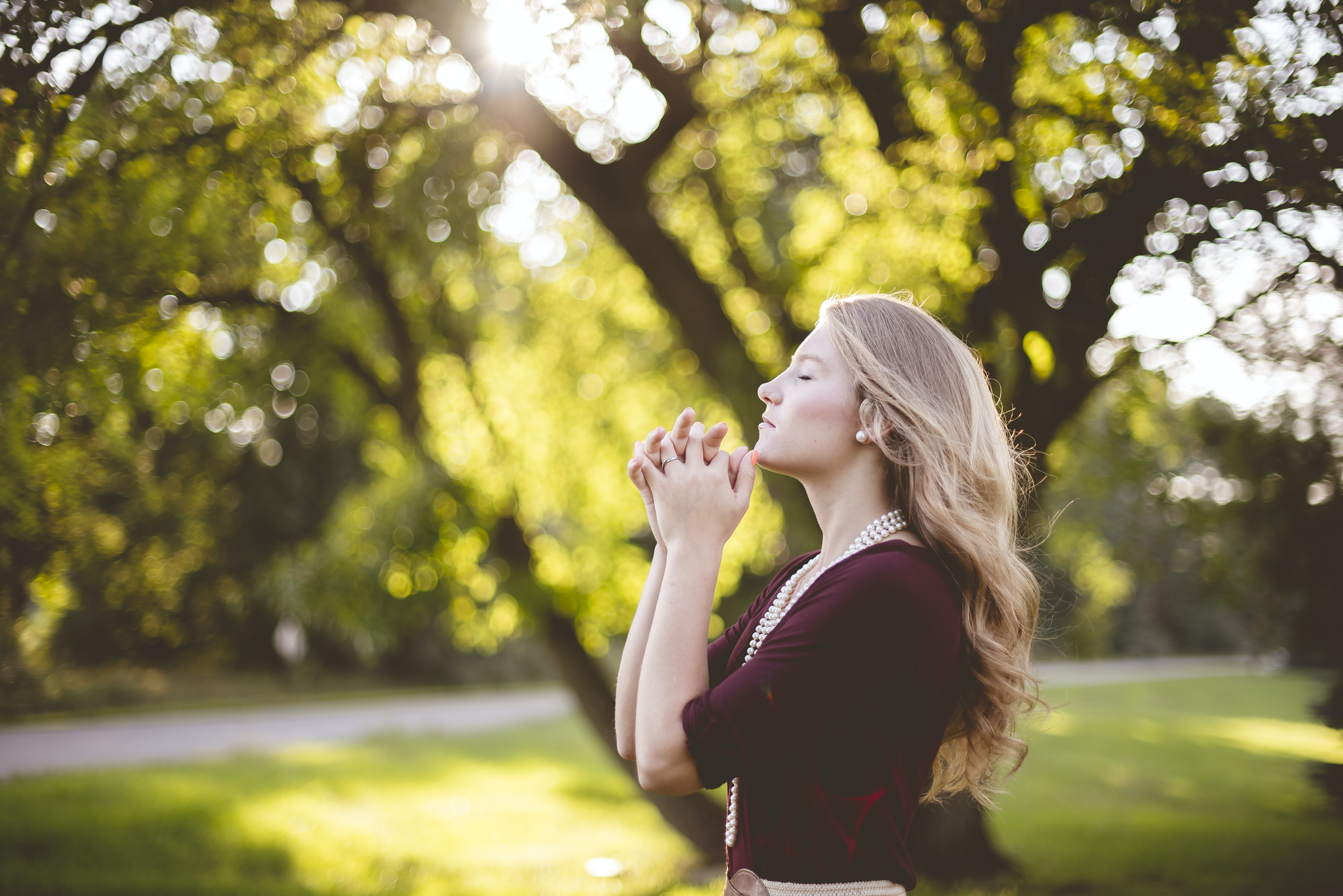 A young blonde woman putting her hands together in a gesture of prayer in a park