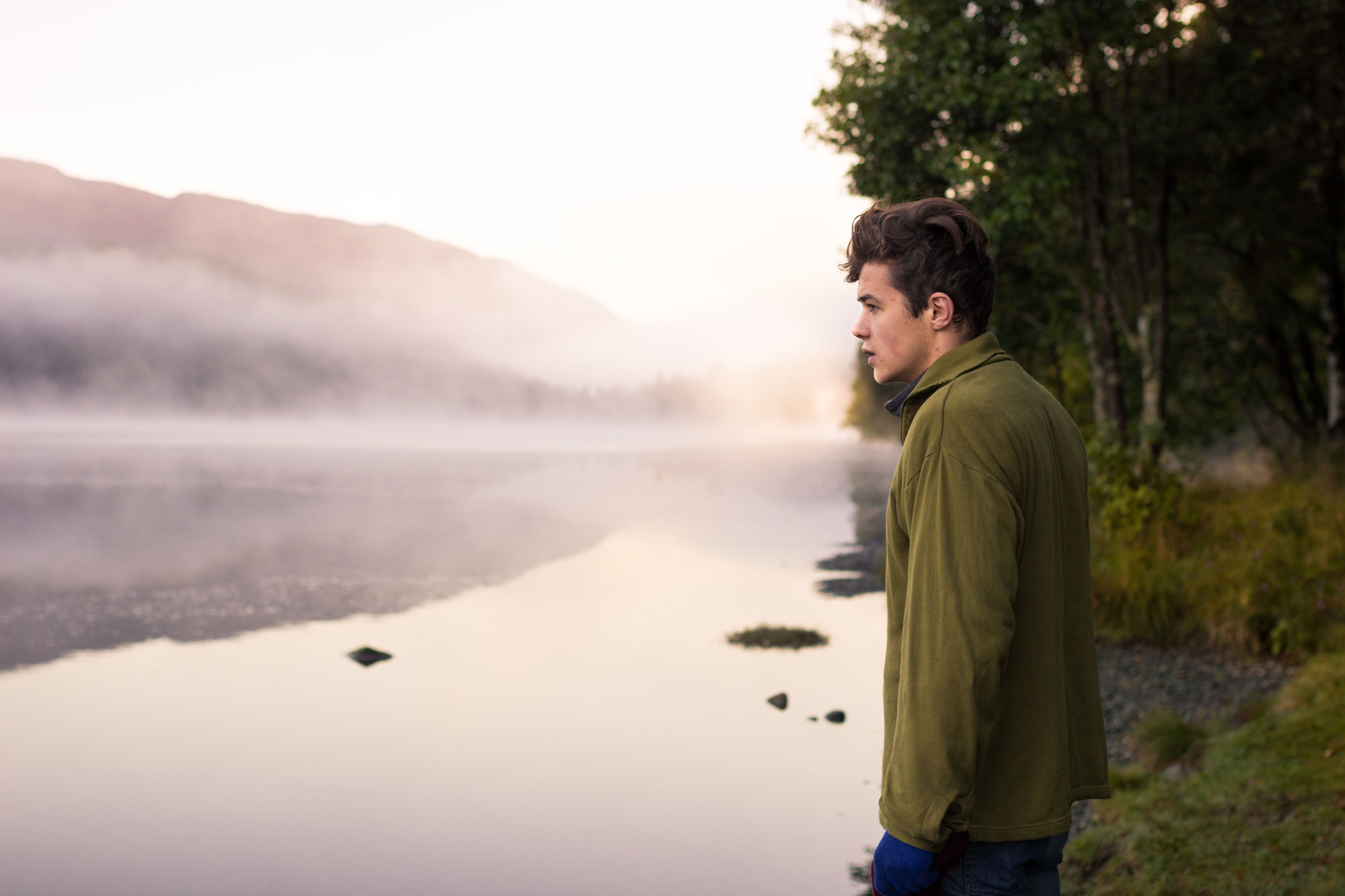 Man stands on the short of a serene foggy lake near the woods