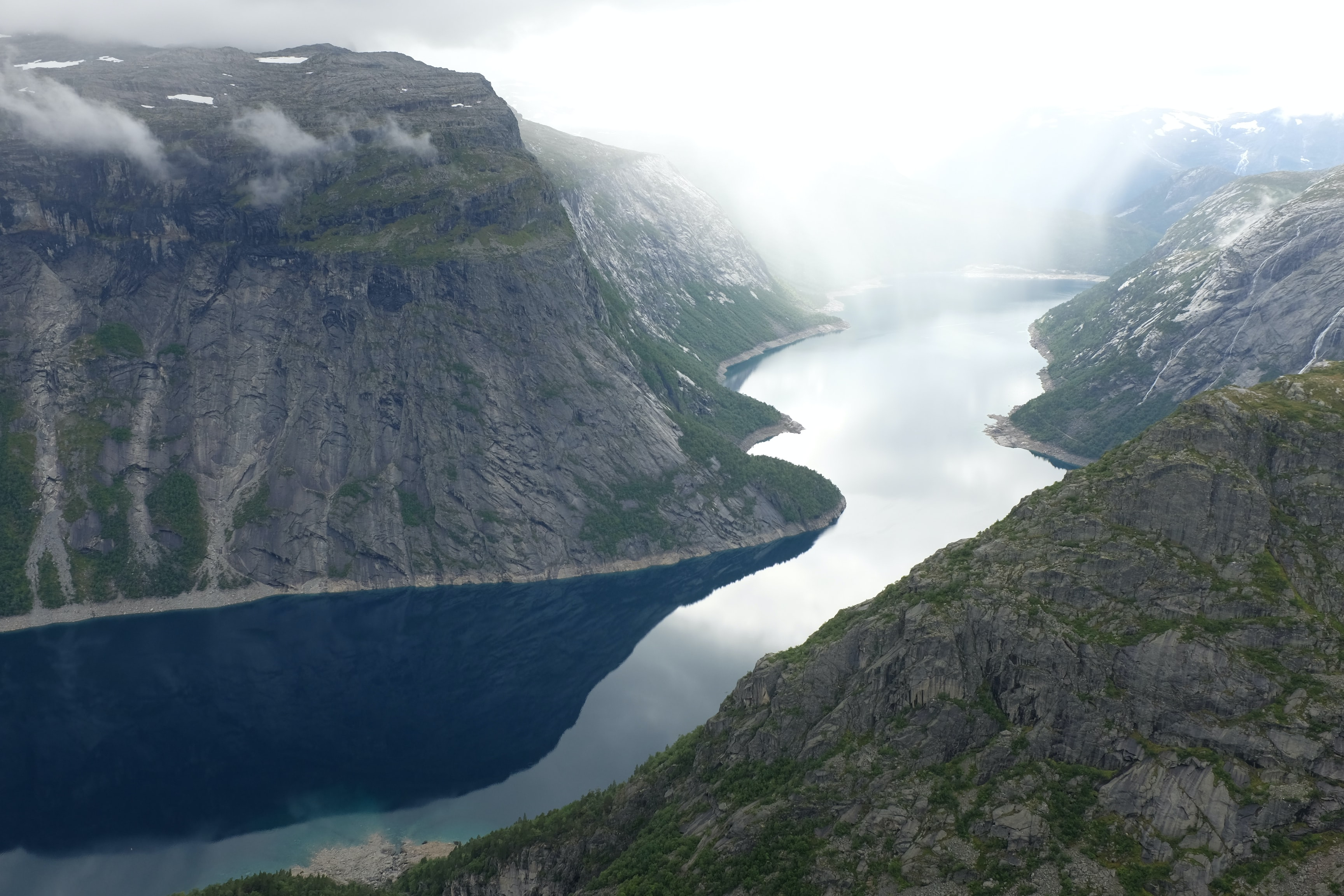 Calm valley river sits between lush mountains in Trolltunga