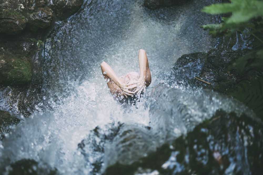 high-angle photography of woman bathing below waterfalls during daytime